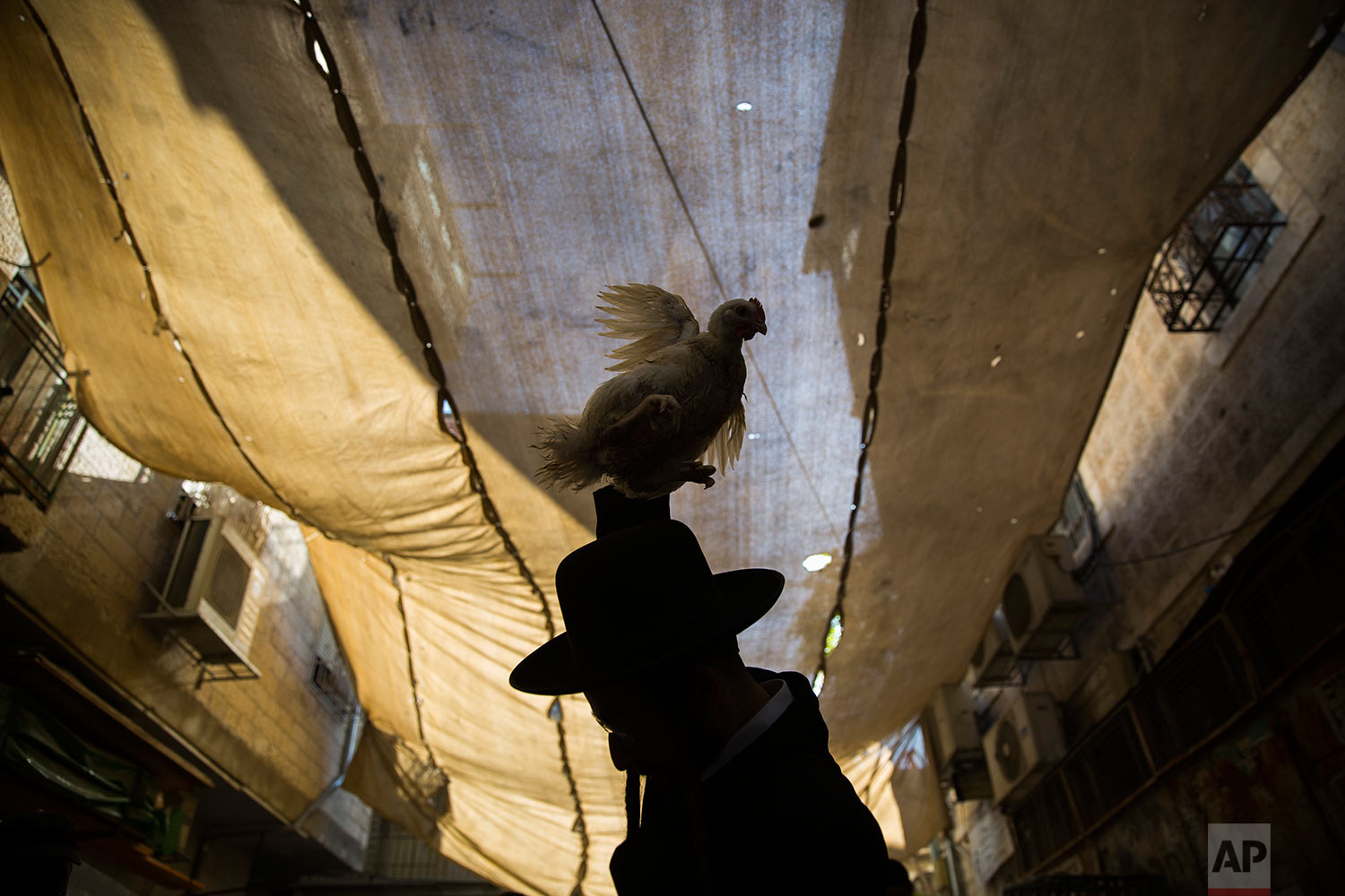 An ultra-Orthodox Jewish man swings a chicken over his head as part of the Kaparot ritual in Jerusalem, Wednesday, Sept. 27, 2017. (AP Photo/Oded Balilty)