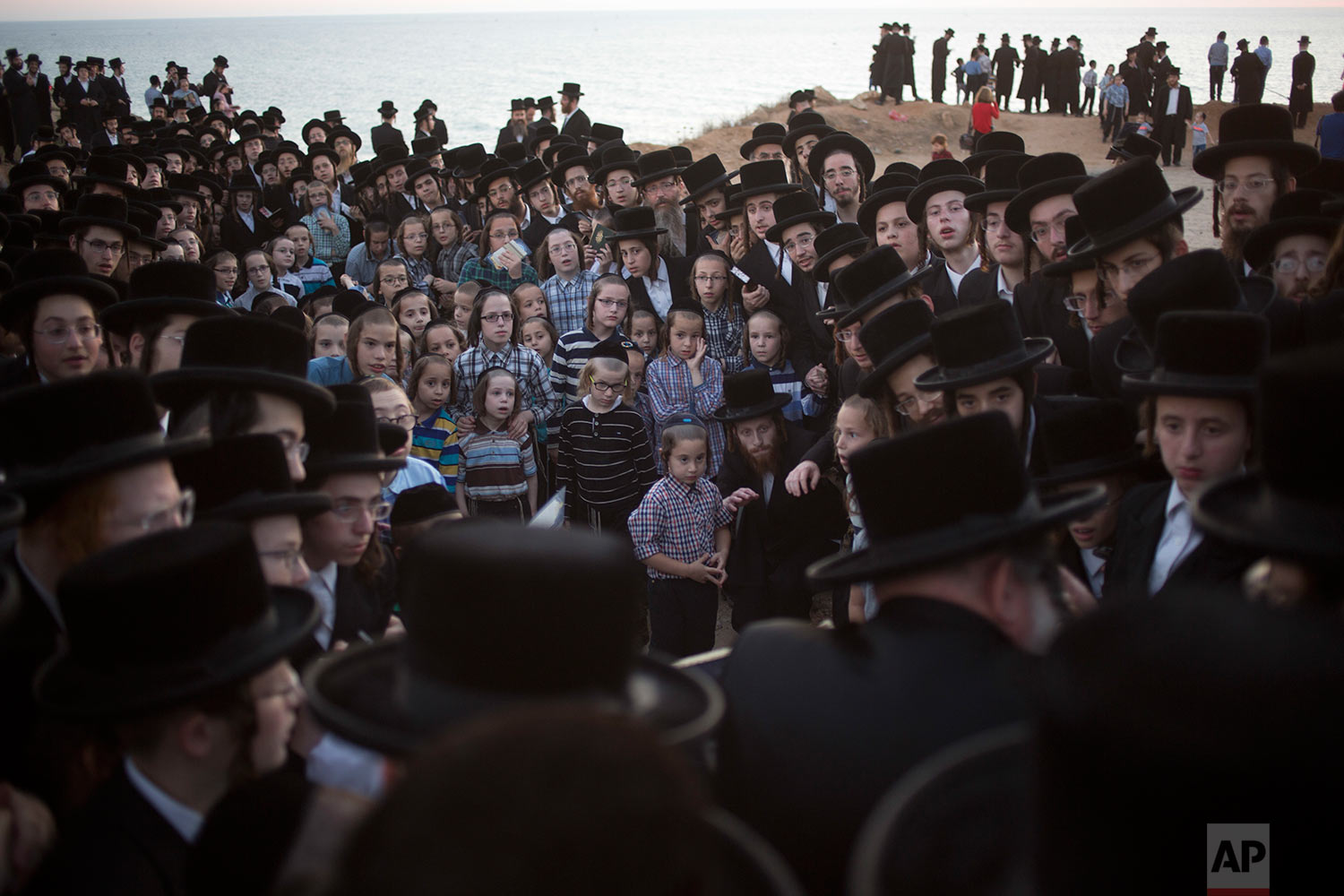 Ultra-Orthodox Jewish men of the Vizhnitz Hassidic sect listen to their rabbi on a hill overlooking the Mediterranean Sea as they participate in a Tashlich ceremony in Herzeliya, Israel, Thursday, Sept. 28, 2017. (AP Photo/Ariel Schalit)