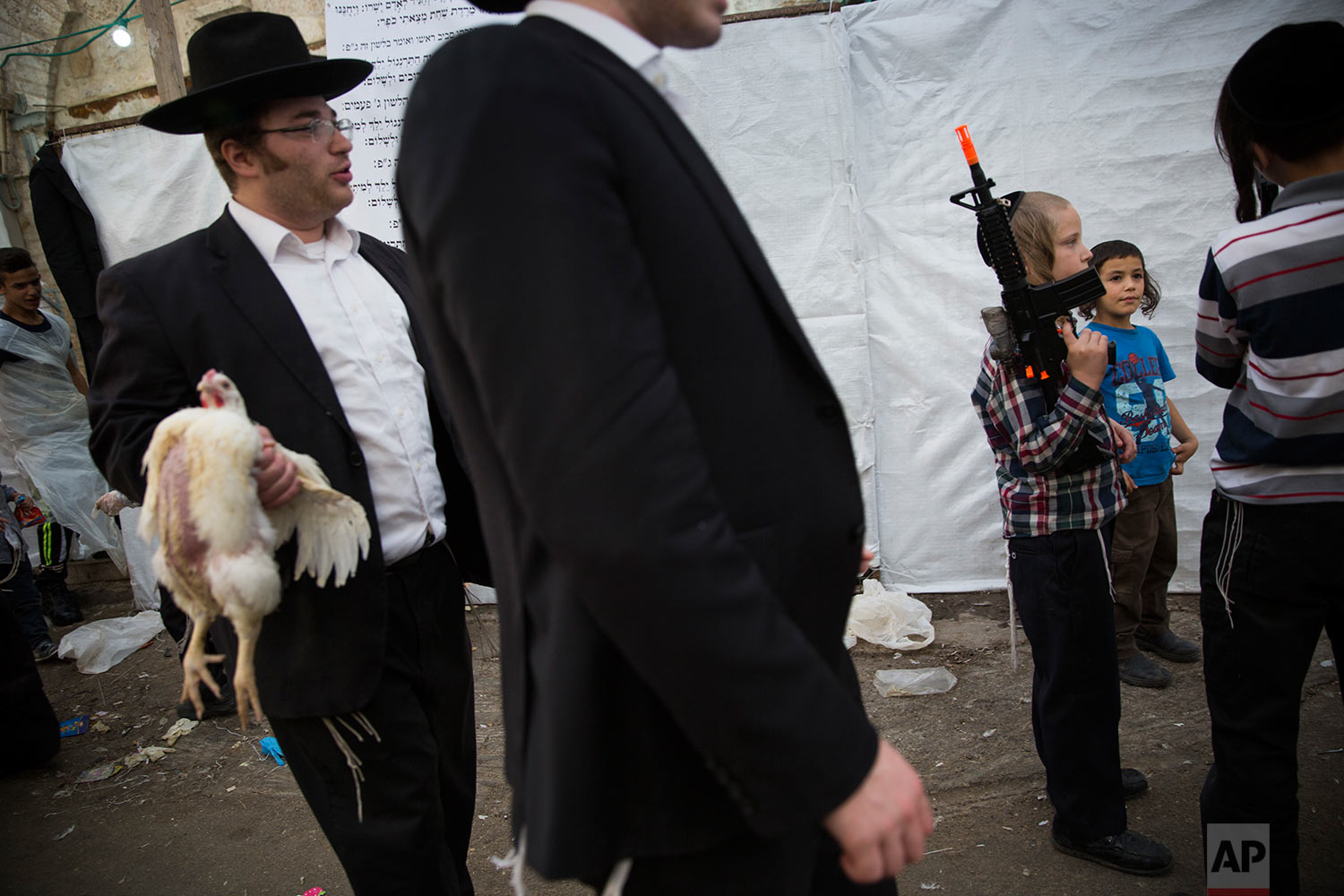 An ultra-Orthodox Jewish man holds a chicken to be used during the Kaparot ritual, as a child holds a toy gun, in Jerusalem, Wednesday, Sept. 27, 2017. (AP Photo/Oded Balilty)