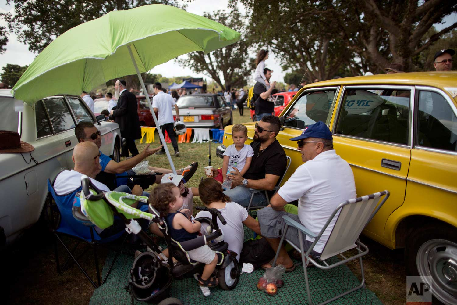 "People sits next to their antique cars during the 31st annual ""Five Club"" collectors car meeting in Ramat Gan, Israel, Friday, Oct. 6, 2017. (AP Photo/Oded Balilty)"