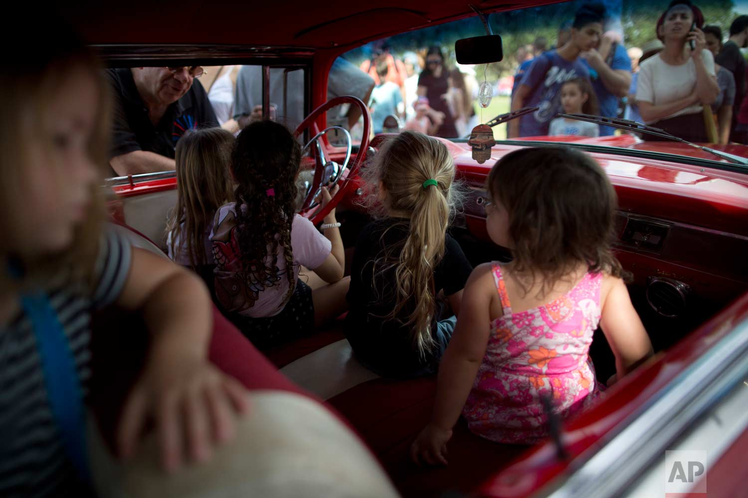 "Children sit in their grandfather's antique car during the 31st annual ""Five Club"" collectors car meeting in Ramat Gan, Israel, Friday, Oct. 6, 2017. (AP Photo/Oded Balilty)"