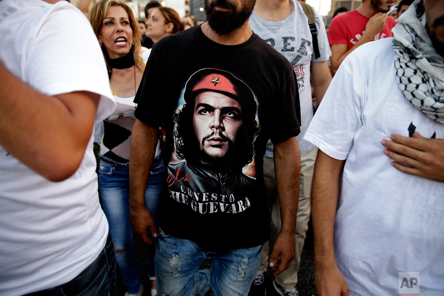 A Lebanese activist wears a portrait of ''Che Guevara'' as others chant slogans during a protest against the trash crisis and government corruption, in downtown Beirut, Lebanon, Wednesday, Aug. 26, 2015. (AP Photo/Hassan Ammar)