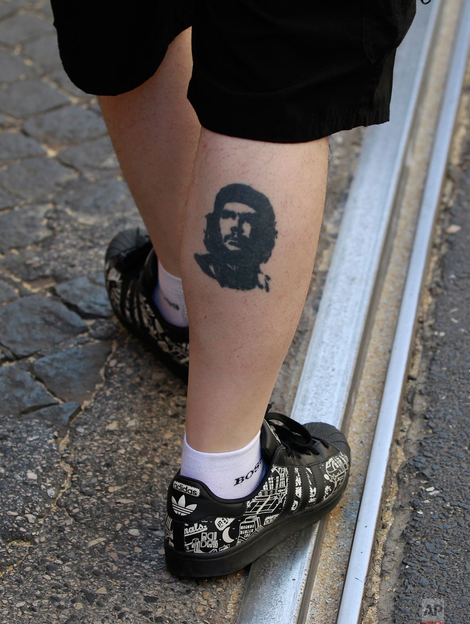 """A protestor wearing a tattoo of Cuba's revolution leader Ernesto """"Che"""" Guevara takes part in a demonstration in Lisbon against the government's plans of making it easier to lay-off people Thursday, July 28 2011. (AP Photo/Armando Franca)"""