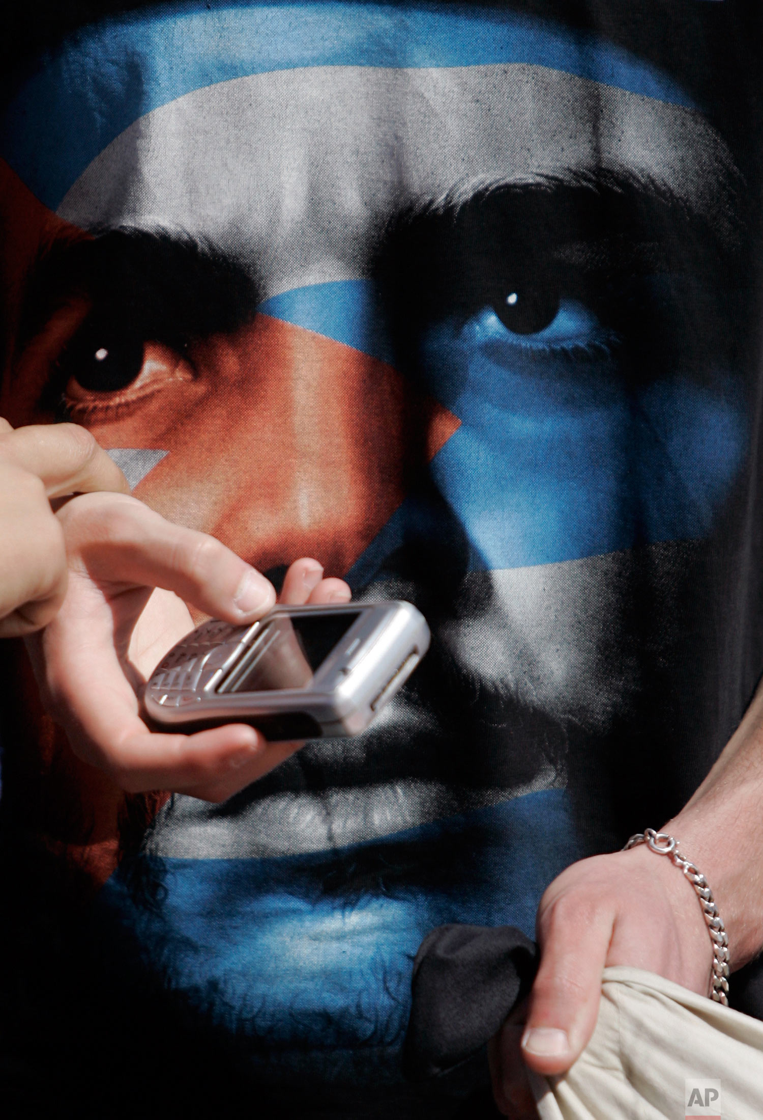 A young man wearing a T-shirt with an image of Cuban revolution leader Ernesto Che Guevara, shows a cellular phone to a friend during a Workers' Day march Thursday, May 1 2008, in Lisbon. (AP Photo/Armando Franca)
