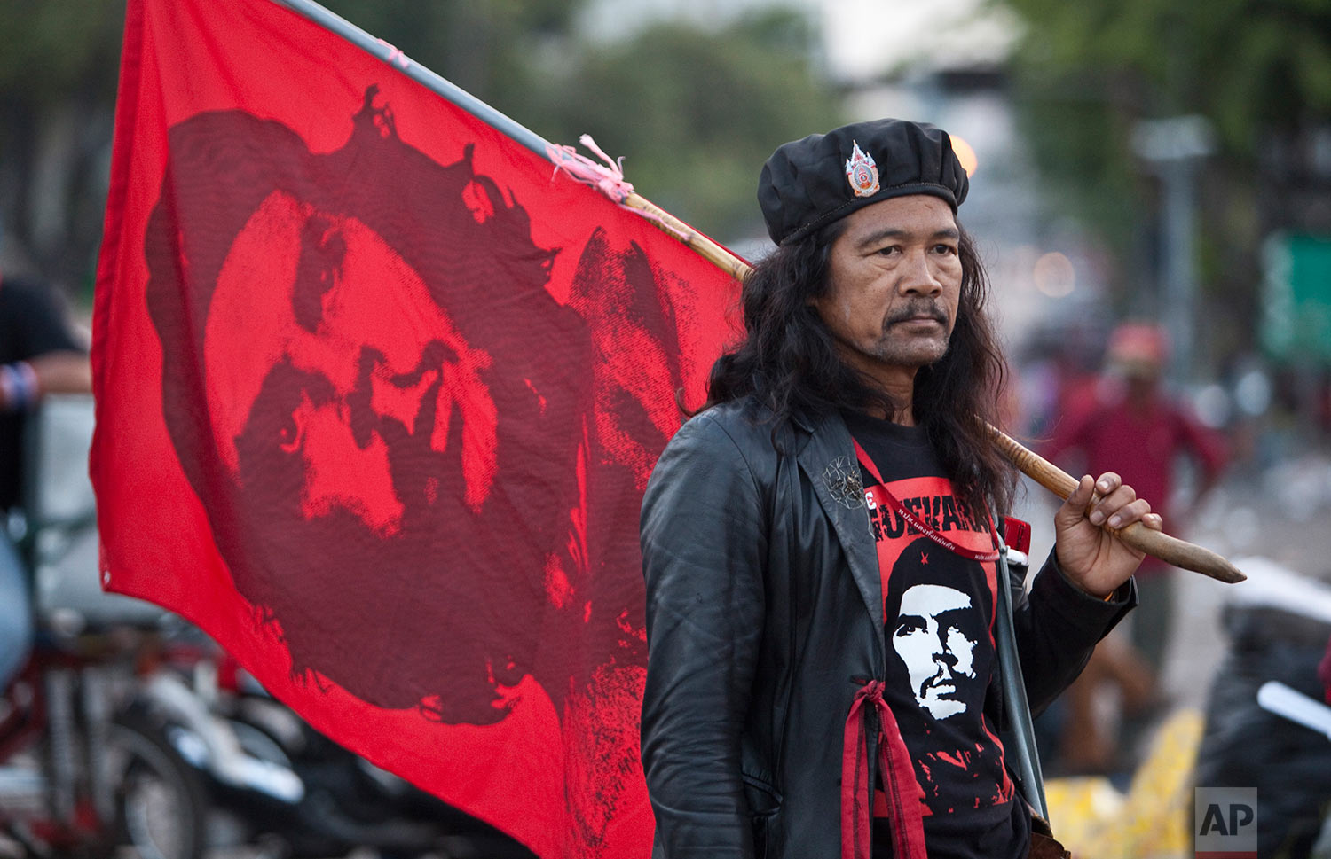 """A """"Red Shirt"""" demonstrator carries a flag of Cuban revolutionary Che Guevara as he and others wait to donate blood Tuesday, March 16, 2010, at an anti-government rally in Bangkok, Thailand. (AP Photo/David Longstreath)"""