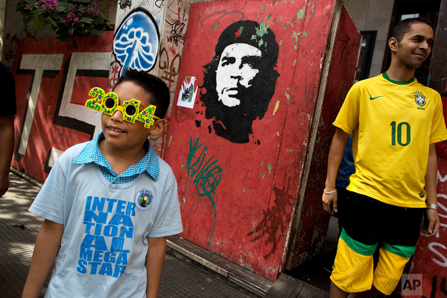 Fans of Brazil stand next to a wall painted with a portrait of famous revolutionary hero Ernesto Che Guevara before the Chile vs. Brazil match during the 2014 soccer World Cup in Sao Paulo, Brazil, Saturday, June 28, 2014.(AP Photo/Rodrigo Abd)