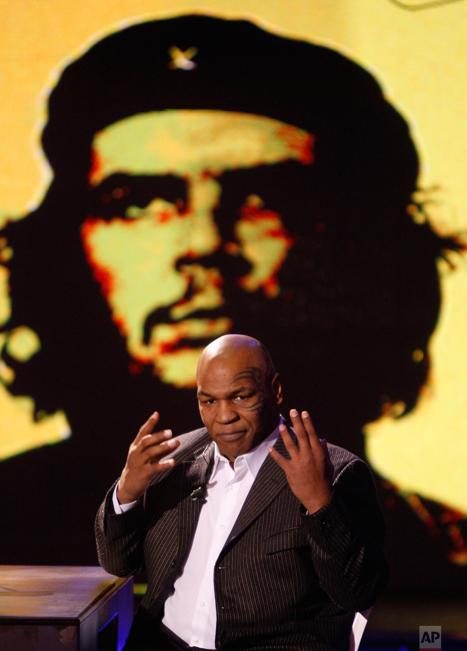 """Former heavyweight boxing champion Mike Tyson reacts as a picture of Che Guevara is projected on a giant screen, during the taping of the """"Chiambretti Night"""" television show in Milan, Italy, Monday, Jan. 25, 2010. (AP Photo/Luca Bruno)"""