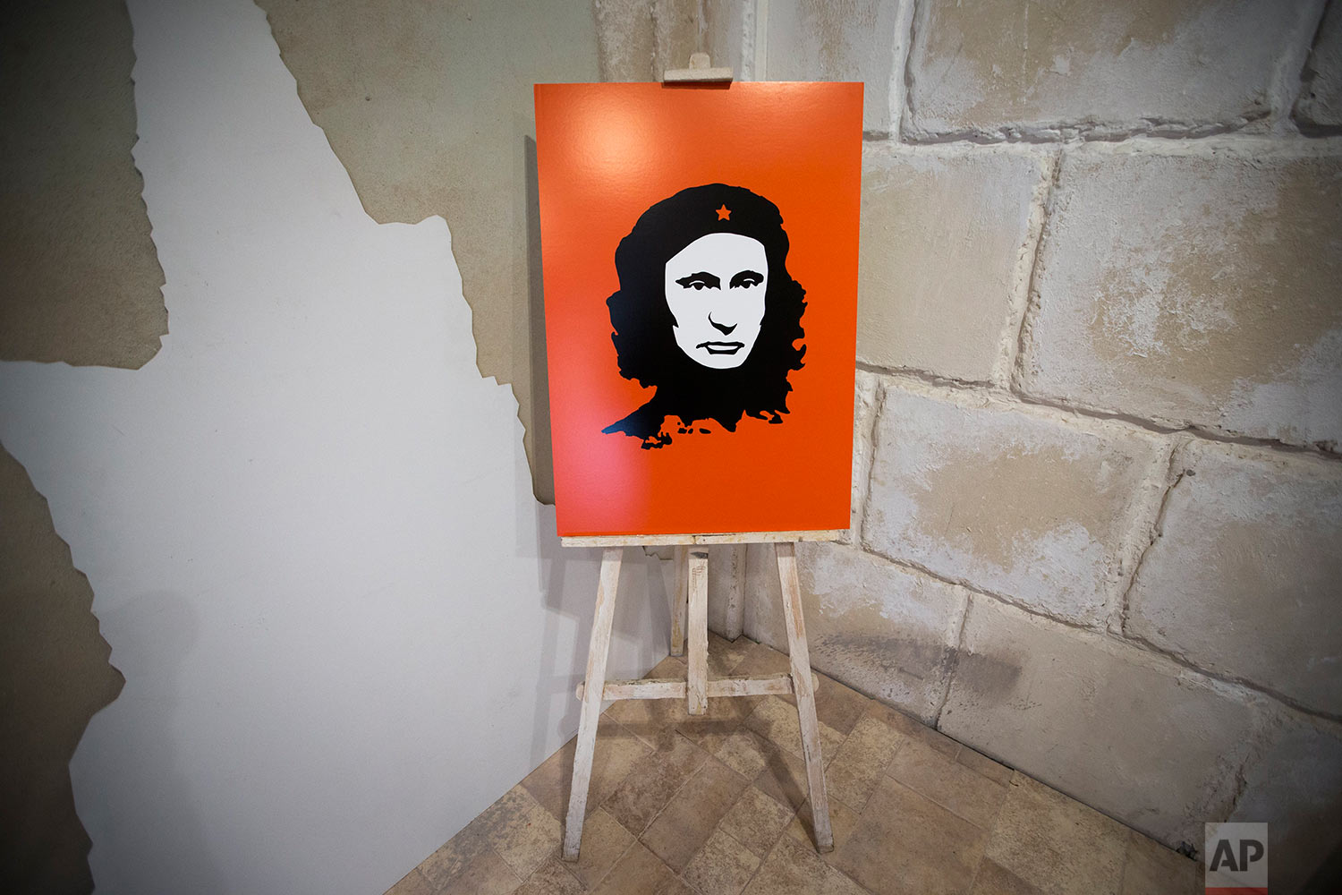 """An artwork showing Russian President Vladimir Putin as Argentine revolutionary leader Ernesto Che Guevara is displayed at the """"Putin Universe"""" exhibition in Moscow, Russia, Wednesday, Oct. 7, 2015. (AP Photo/Pavel Golovkin)"""