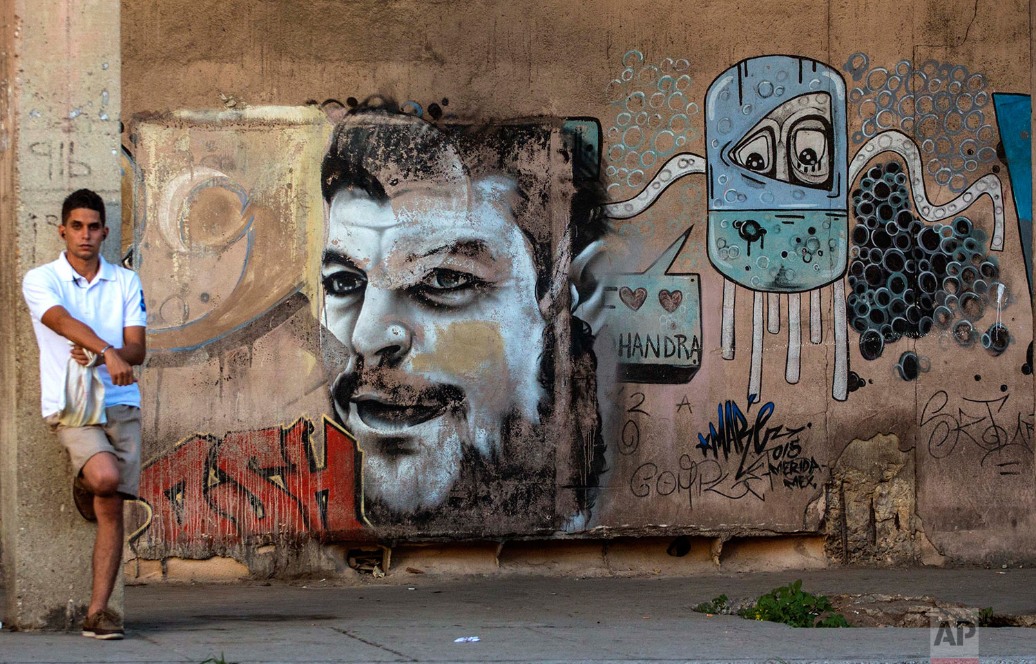 A youth waits at a bus stop beside a mural painting of Che Guevara in Havana, Cuba, Thursday, July 28, 2016. Che Guevara was an Argentine Marxist revolutionary, physician, author, guerrilla leader and major figure of the Cuban Revolution (AP Photo/Desmond Boylan)