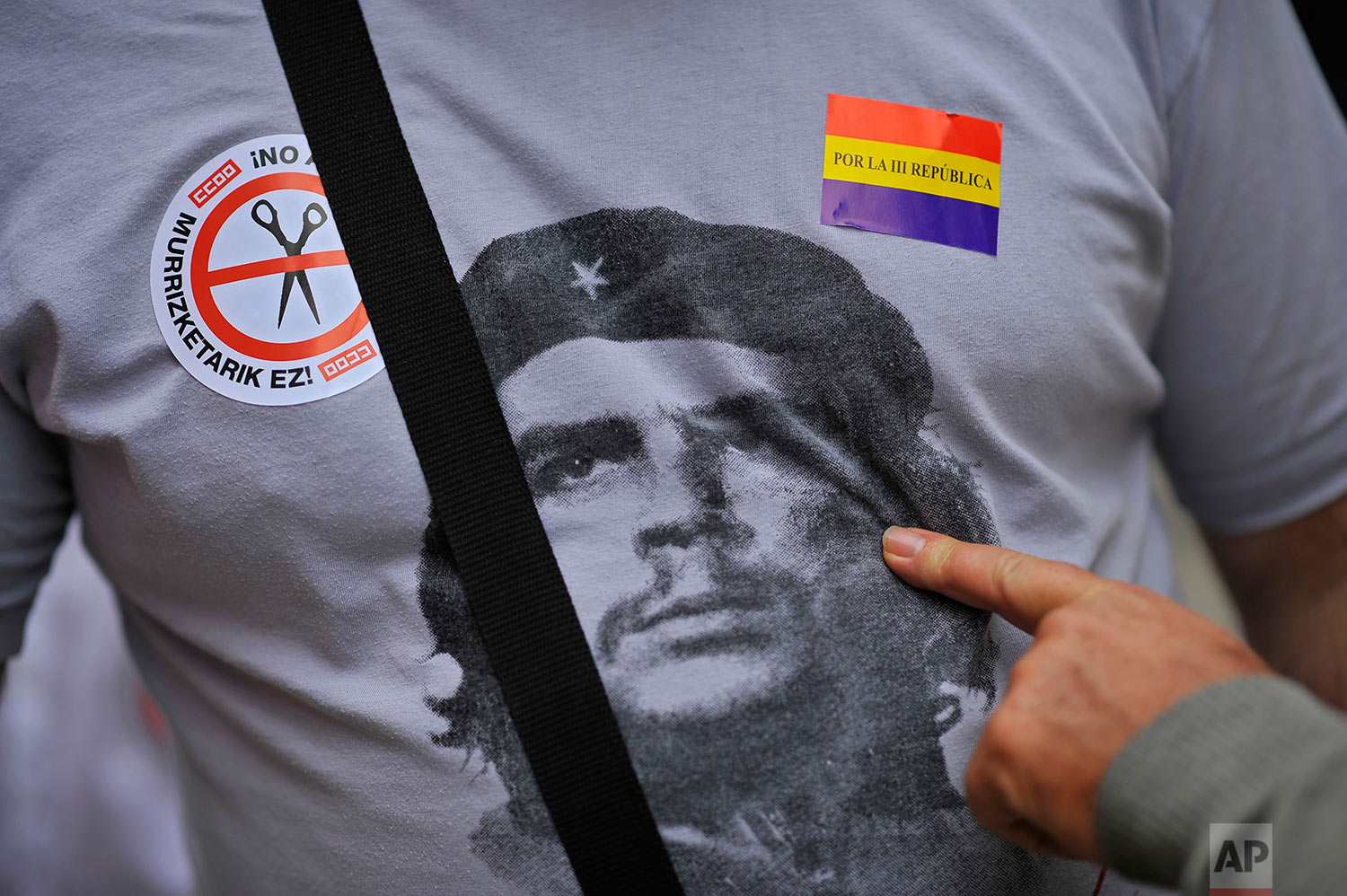 A citizen points to a portrait of ''Che Guevara'' on a shirt of one demonstrator between two stickers, at a protest against the Spanish government's cutback plans, and for a new Spanish Republic, right, in Pamplona, northern Spain, Sunday, Oct. 7, 2012. (AP Photo/Alvaro Barrientos)