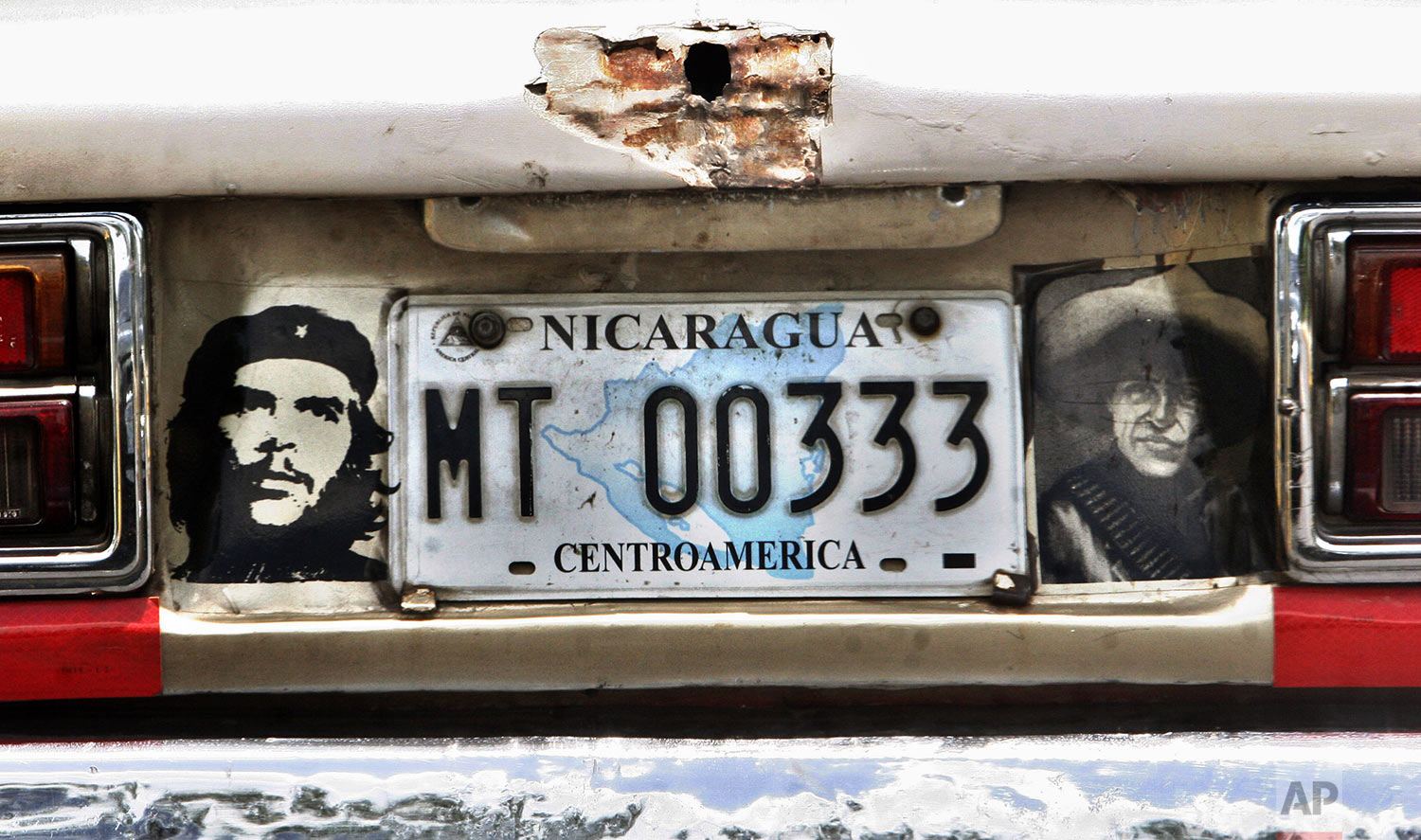"""A car decorated with images of Argentinian revolutionary leader Ernesto """"Che"""" Guevara, left, and Nicaragua's national hero Augusto C. Sandino, right, is seen in Managua, Tuesday, June 26, 2007. (AP Photo/Esteban Felix)"""