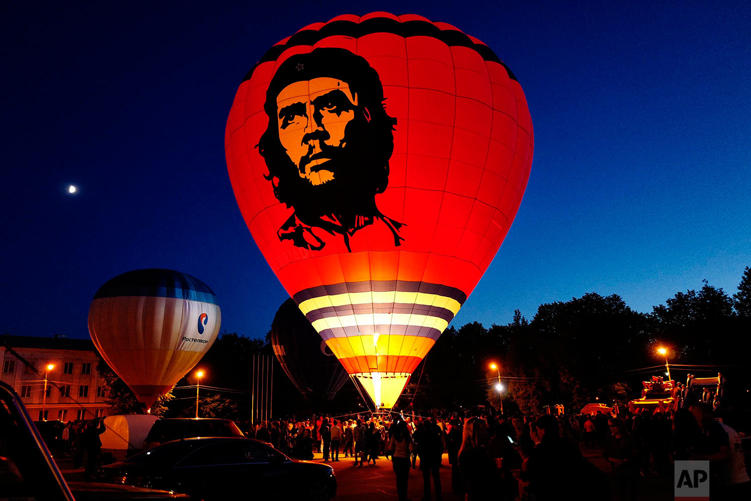 In this photo taken on Monday, June 13, 2016, a hot air balloon with the the image of Argentine revolutionary Che Guevara printed on it's side prepares to lift off during a ballooning festival in Velikiye Luki, Russia . (AP Photo/Maxim Marmur)