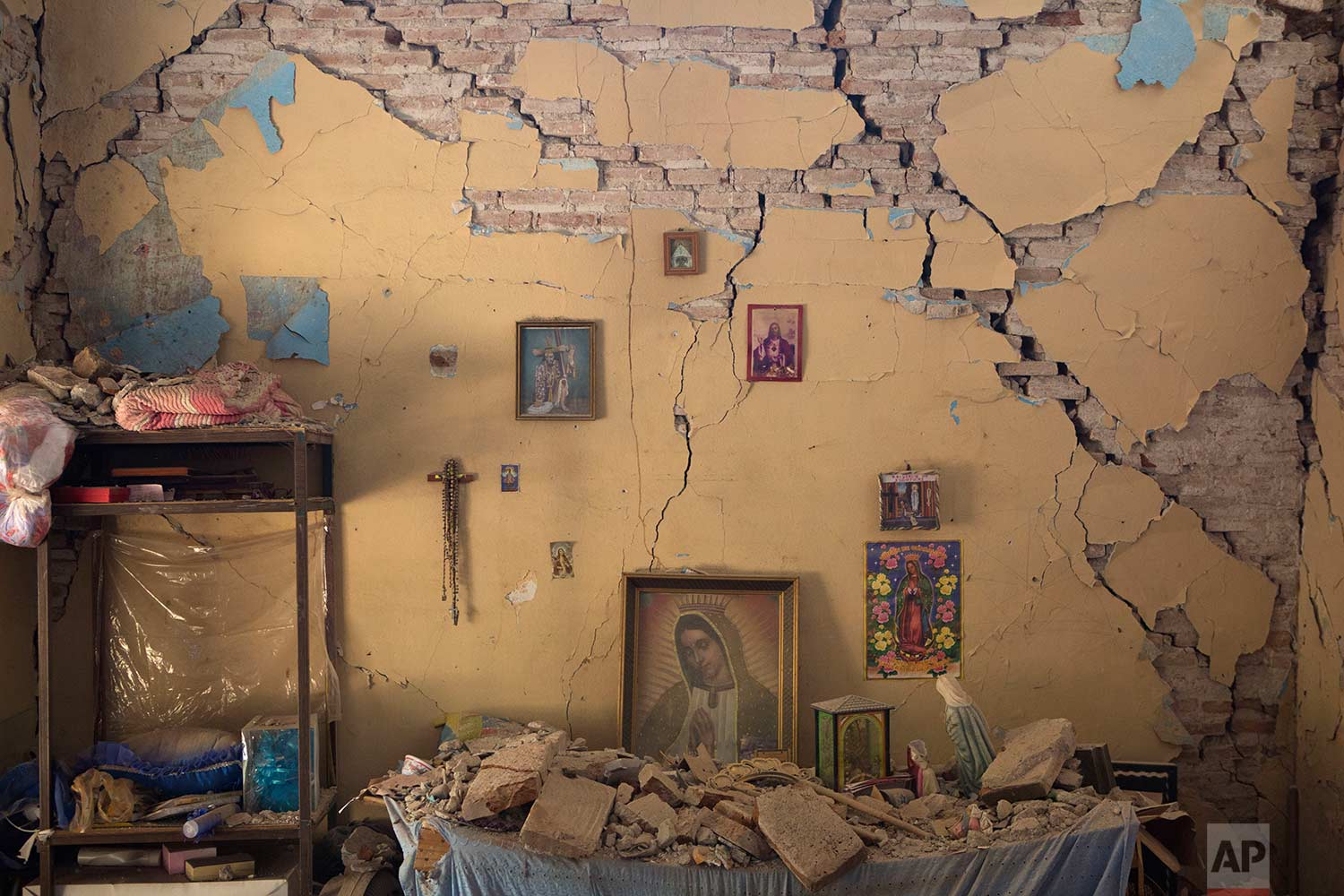 An altar to the Virgin of Guadalupe is covered with fallen debris inside the earth-damaged home where Larissa Garcia, 24, lived with her family in Juchitan, Oaxaca state, Mexico, Saturday, Sept. 9, 2017. (AP Photo/Rebecca Blackwell)