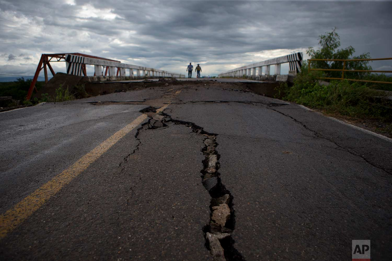 Men walk across the bridge that connects Juchitan to Union Hidalgo in Oaxaca state, Mexico, Sunday, Sept. 10, 2017. While the bridge survived Thursday's magnitude 8.1 earthquake, the road leading up to each side fissured and the supporting walls buckled. (AP Photo/Rebecca Blackwell)