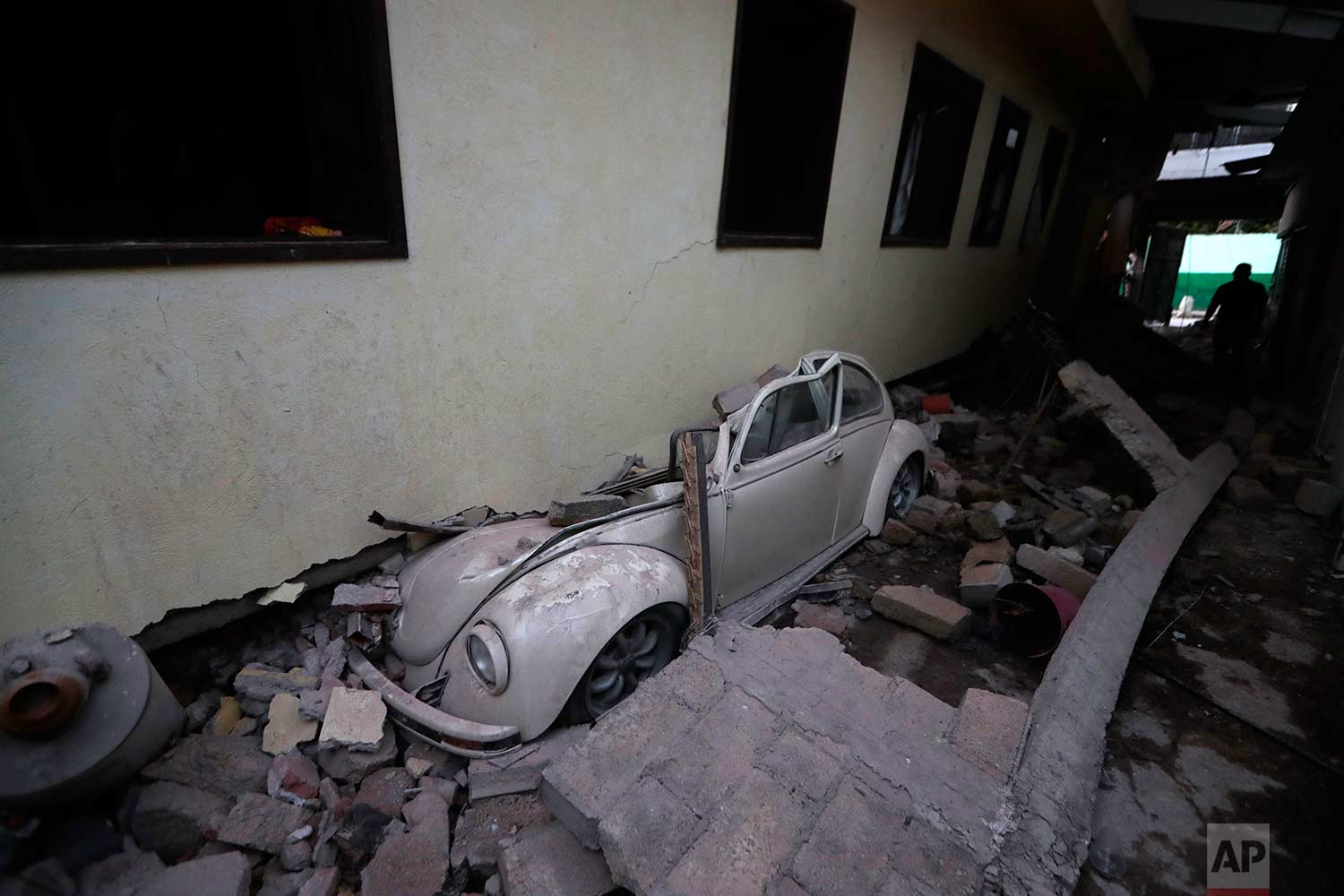 In this Sept. 20, 2017 photo, a car sits crushed from a building felled by a 7.1 earthquake, in Jojutla, Morelos state, Mexico. (AP Photo/Eduardo Verdugo)