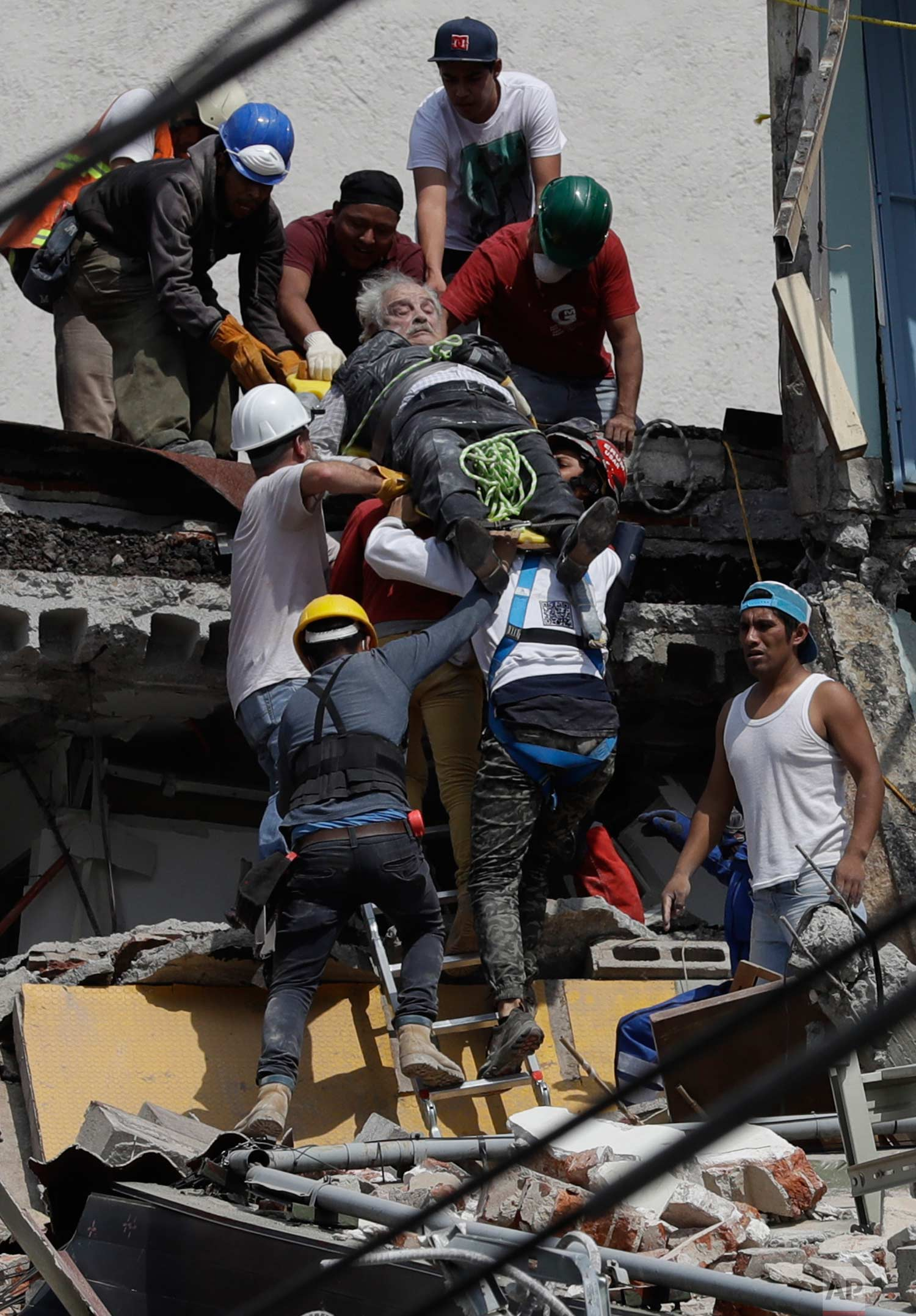 In this Sept. 19, 2017 photo, an injured man is pulled out of a building that collapsed during an earthquake in the Roma Norte neighborhood of Mexico City. (AP Photo/Rebecca Blackwell)