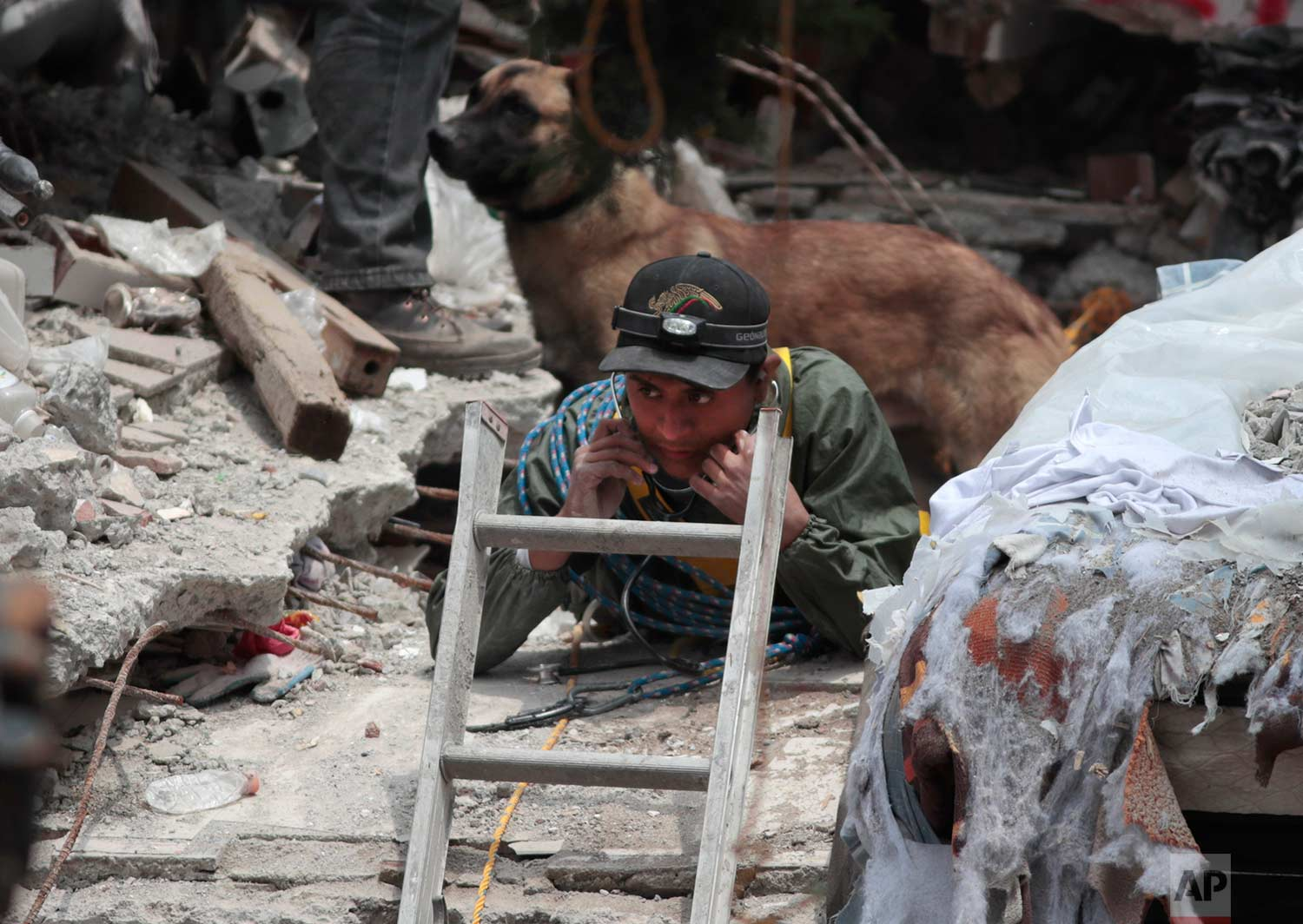A rescue worker listens for signs of a person trapped under the rubble of a building felled by a 7.1 magnitude earthquake, in the Ciudad Jardin neighborhood of Mexico City, Thursday, Sept. 21, 2017. (AP Photo/Eduardo Verdugo)