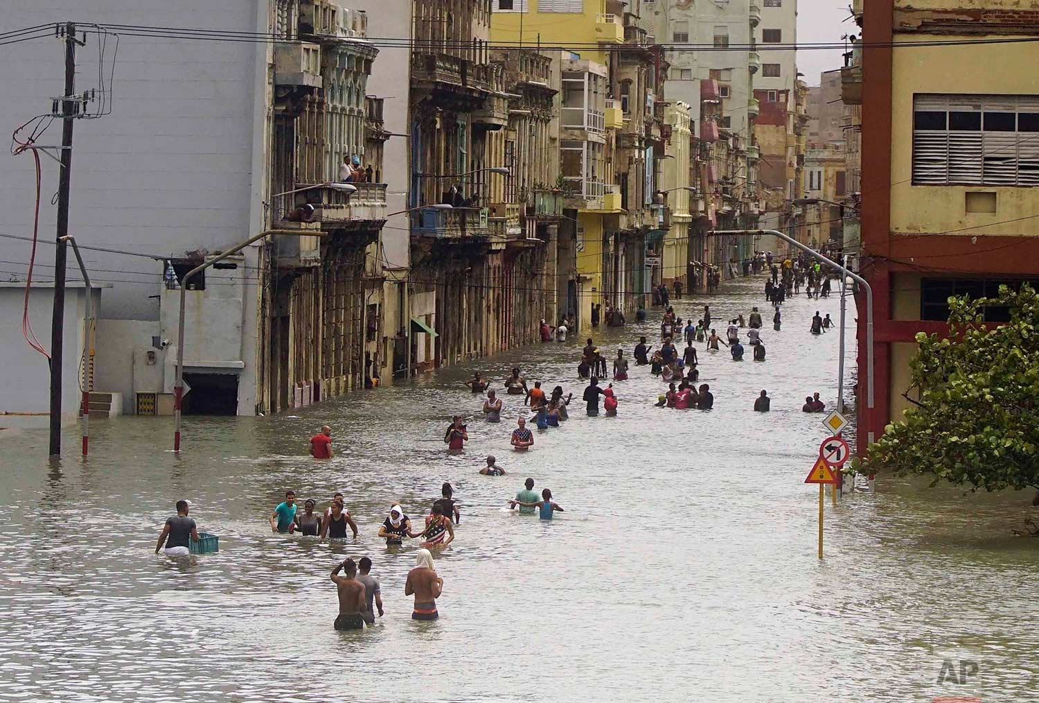 People move through flooded streets in Havana after the passage of Hurricane Irma, in Cuba, Sunday, Sept. 10, 2017. (AP Photo/Ramon Espinosa)