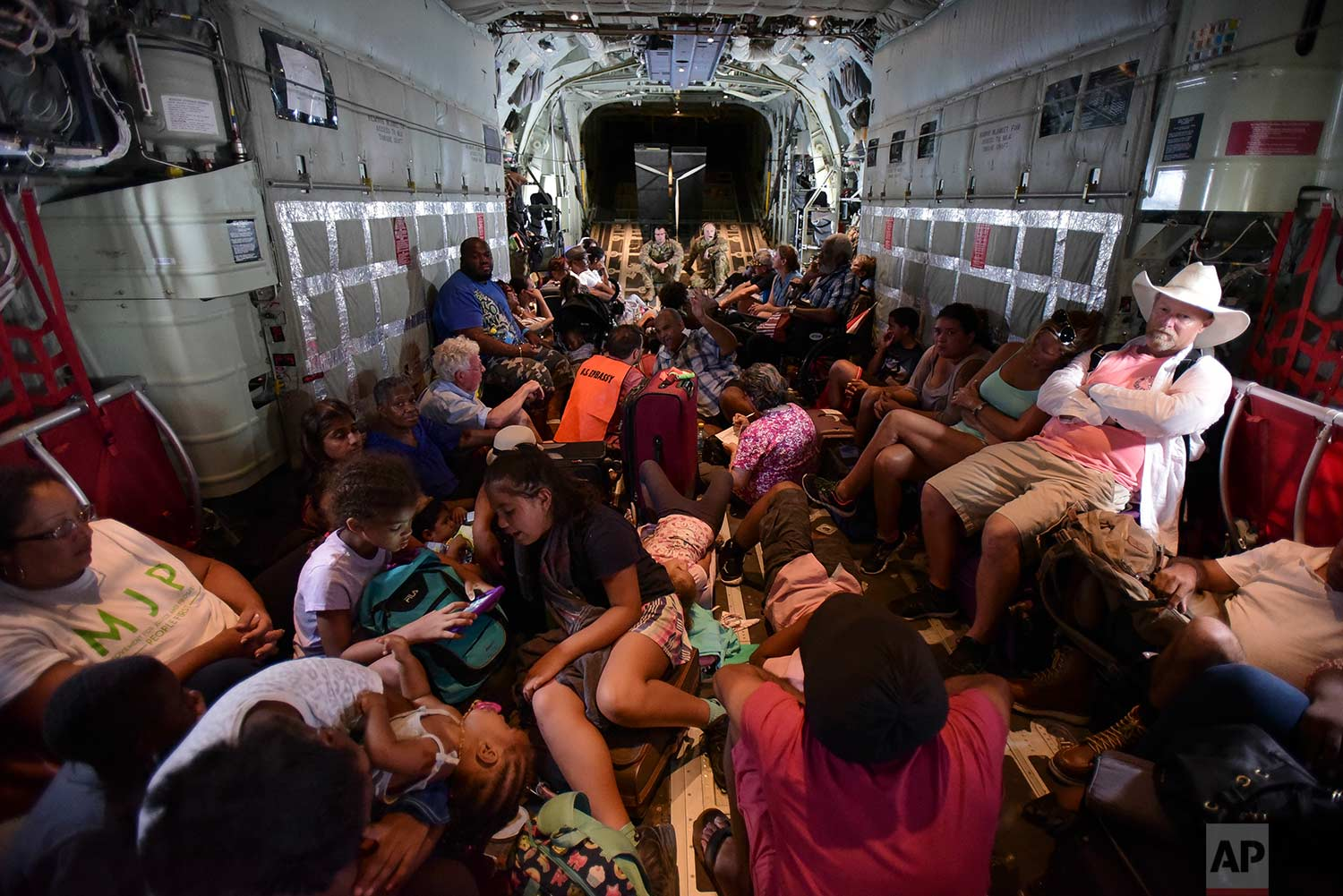 In this Tuesday, Sept. 12, 2017 photo, U.S. Air force personnel evacuate U.S. citizens from St. Martin, aboard an aircraft after the passage of Hurricane Irma. (AP Photo/Carlos Giusti)
