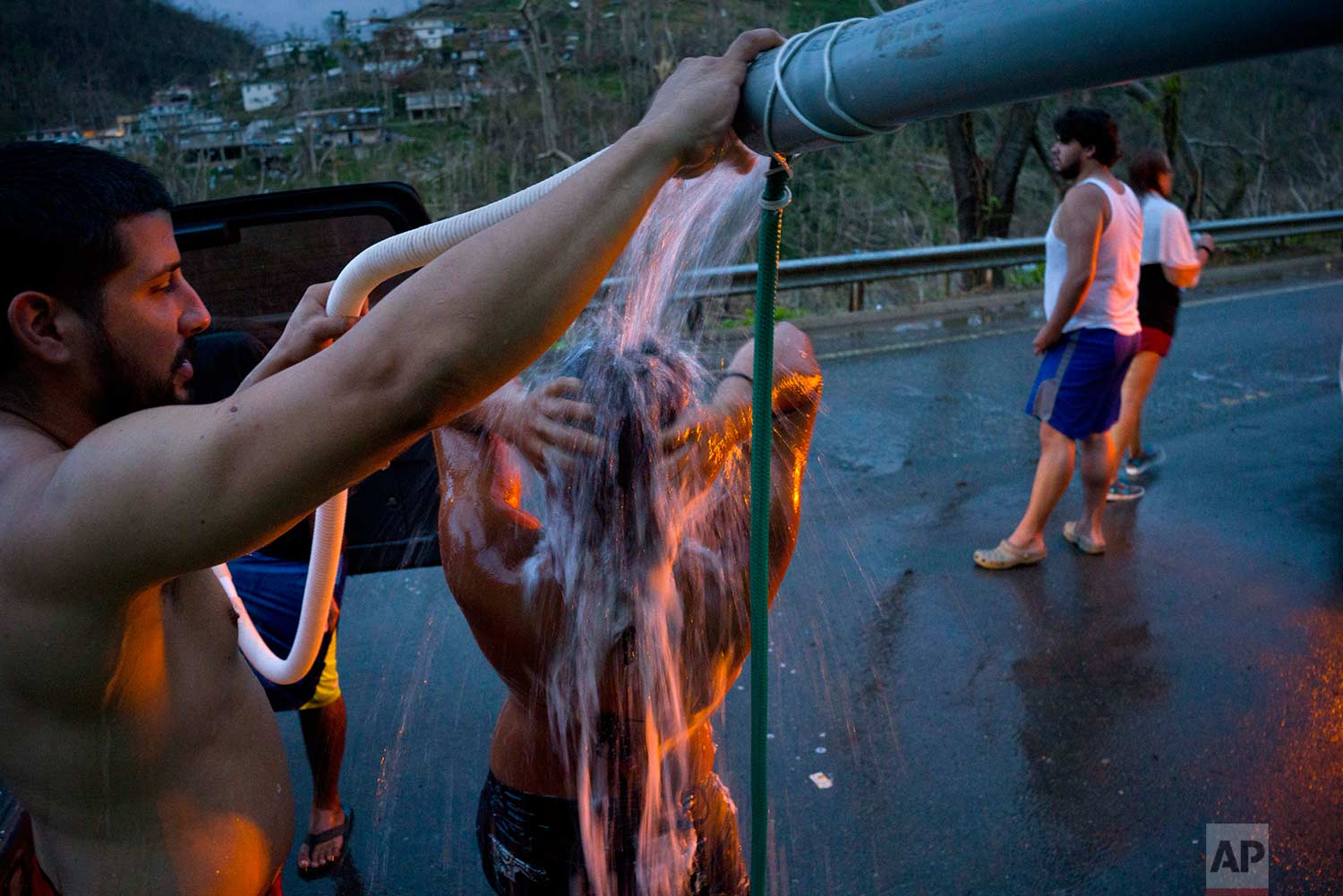 People affected by Hurricane Maria bathe in water pipes from a creek in the mountains, in Naranjito, Puerto Rico, Thursday, Sept. 28, 2017. (AP Photo/Ramon Espinosa)