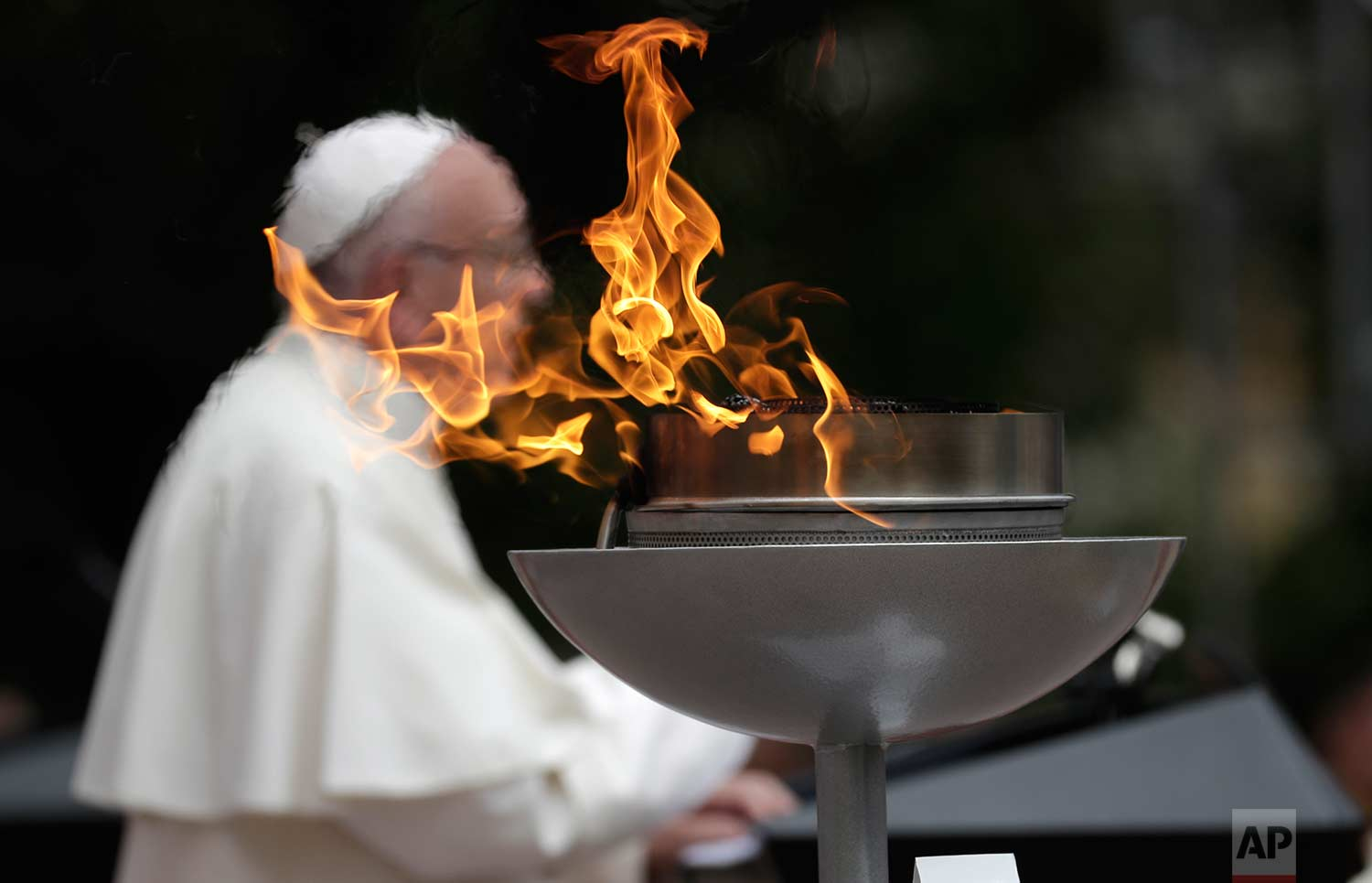 "A ""reconciliation flame"" burns as Pope Francis speaks during a ceremony at the presidential palace in Bogota, Colombia, Thursday, Sept. 7, 2017. (AP Photo/Andrew Medichini)"