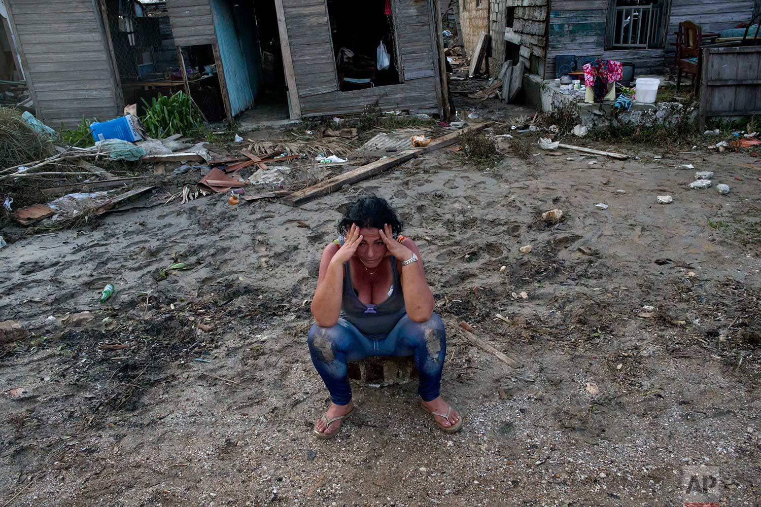 A despondent Mariela Leon sits in front of her flood damaged home after the passing of Hurricane Irma, in Isabela de Sagua, Cuba, Monday, Sept. 11, 2017. (AP Photo/Ramon Espinosa)