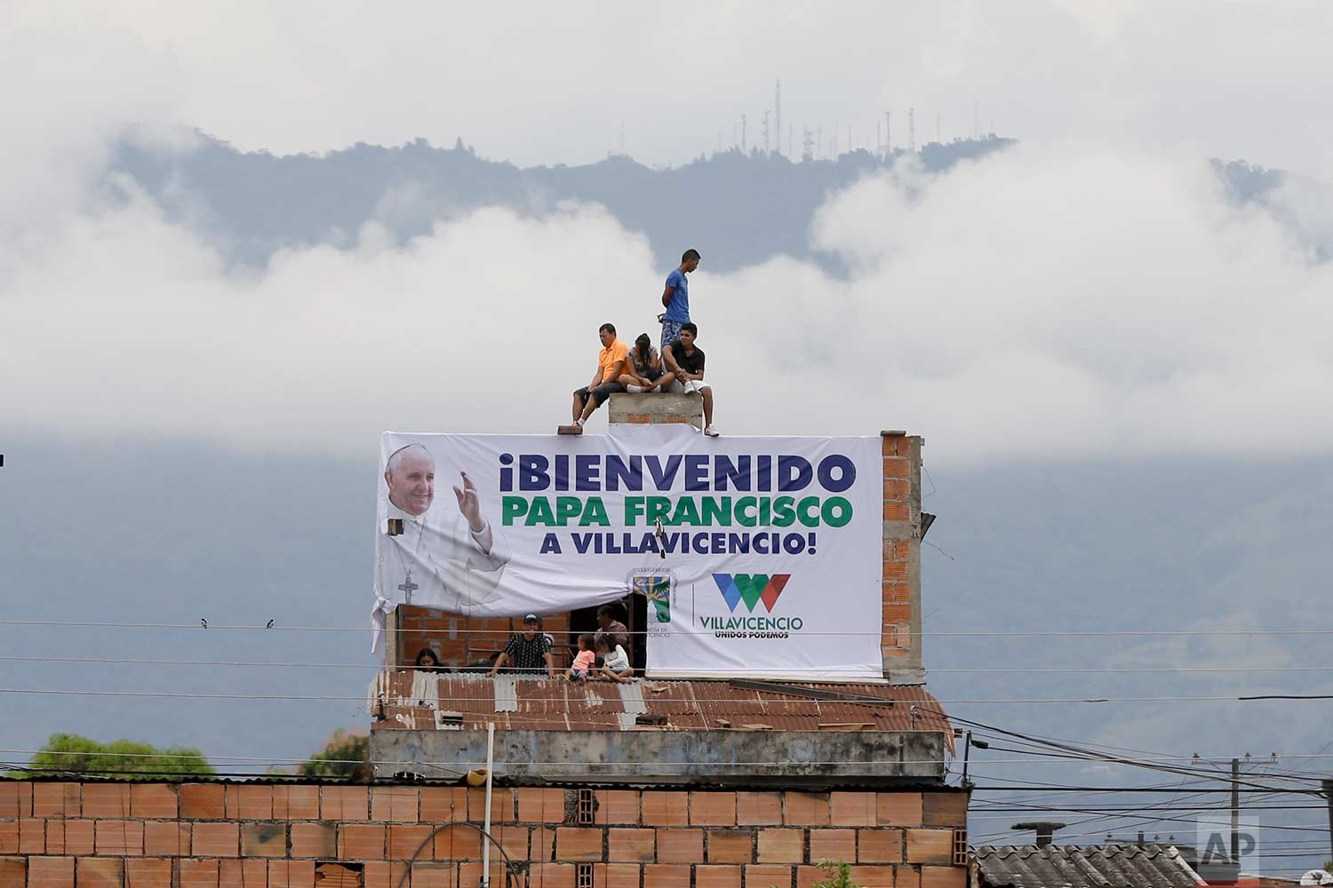 "Residents sit on top of a home to get a better view of Pope Frances celebrating Mass at a park in Villavicencio, Colombia, Friday, Sept. 8, 2017. The sign reads in Spanish ""Pope Francis, Welcome to Villavicencio!"" (AP Photo/Ricardo Mazalan)"