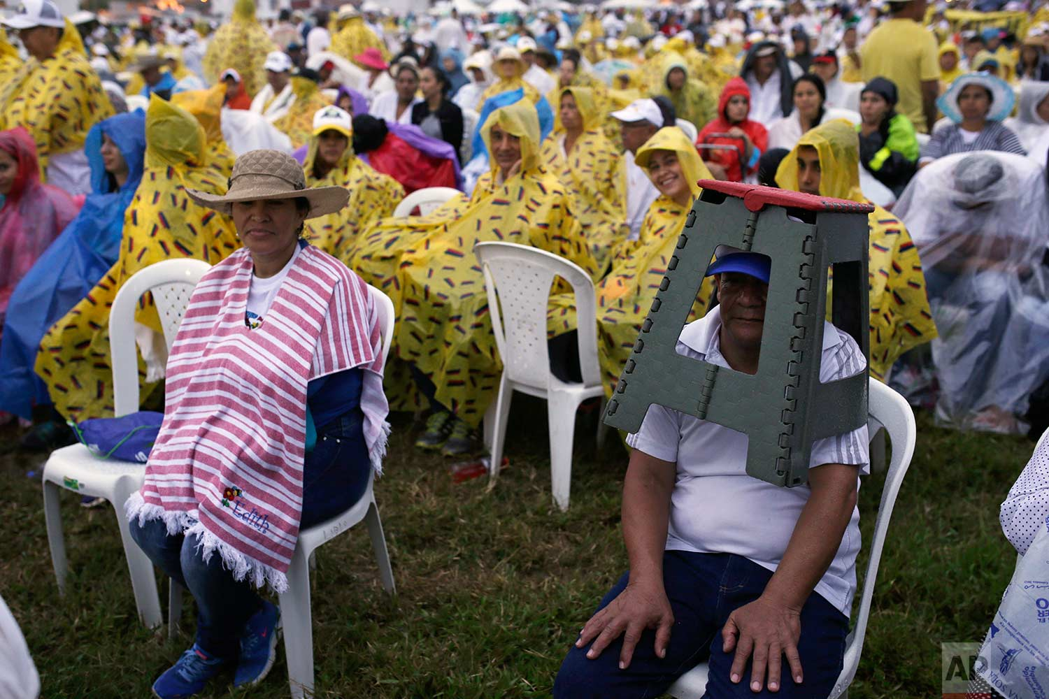 In this Friday, Sept. 8, 2017 photo, people wait under a light rain for the start of a Holy Mass celebrated by Pope Francis in Villavicencio, Colombia. (AP Photo/Ricardo Mazalan)