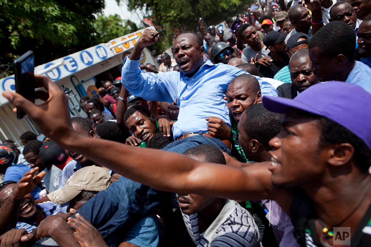 Former presidential candidate Moise Jean-Charles, from the Platform Pitit Dessalines party, is carried by supporters after national police officers attempted to detain him in Delmas, a district of Port-au-Prince, Haiti, Wednesday, Sept. 13, 2017. (AP Photo/Dieu Nalio Chery)