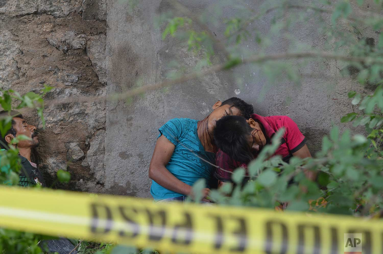 EDS NOTE: GRAPHIC CONTENT - The bodies of three men, two of them teenagers, lie against a wall under an overpass on a highway after being shot in the town of Coyuca, near Acapulco, Guerrero state, Mexico, Tuesday, Sept. 12, 2017. (AP Photo/Bernandino Hernandez)