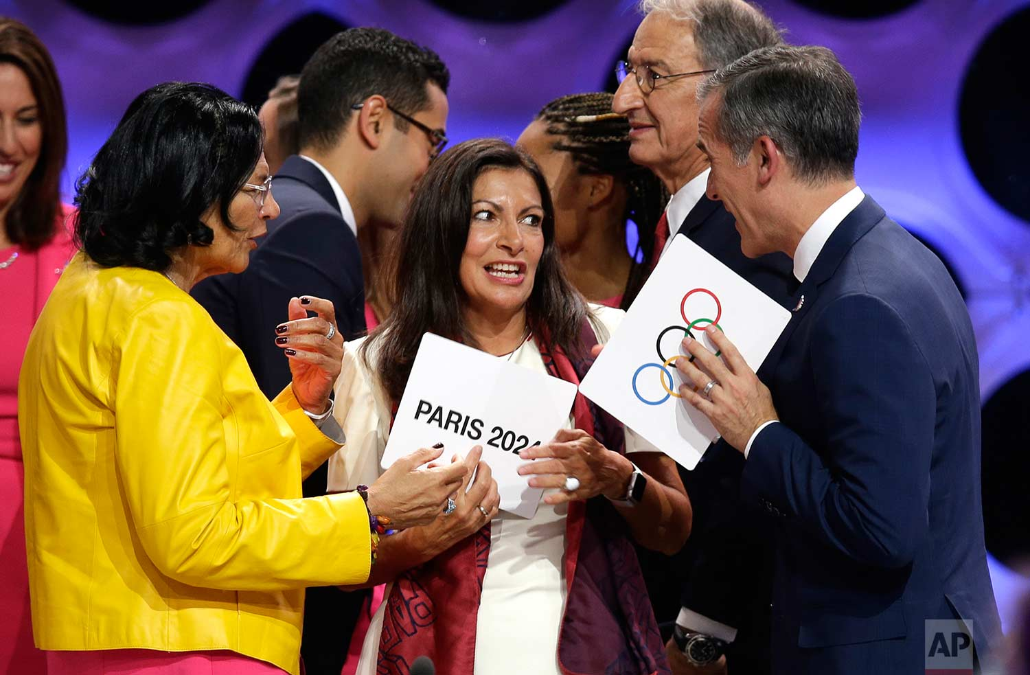 Paris Mayor Anne Hidalgo, center, speaks with Los Angeles Mayor Eric Garrett, right, and Los Angeles International Olympic Committee member Anita DeFrantz, left, at the end of the IOC session in Lima, Peru, Wednesday, Sept. 13, 2017. (AP Photo/Martin Mejia)