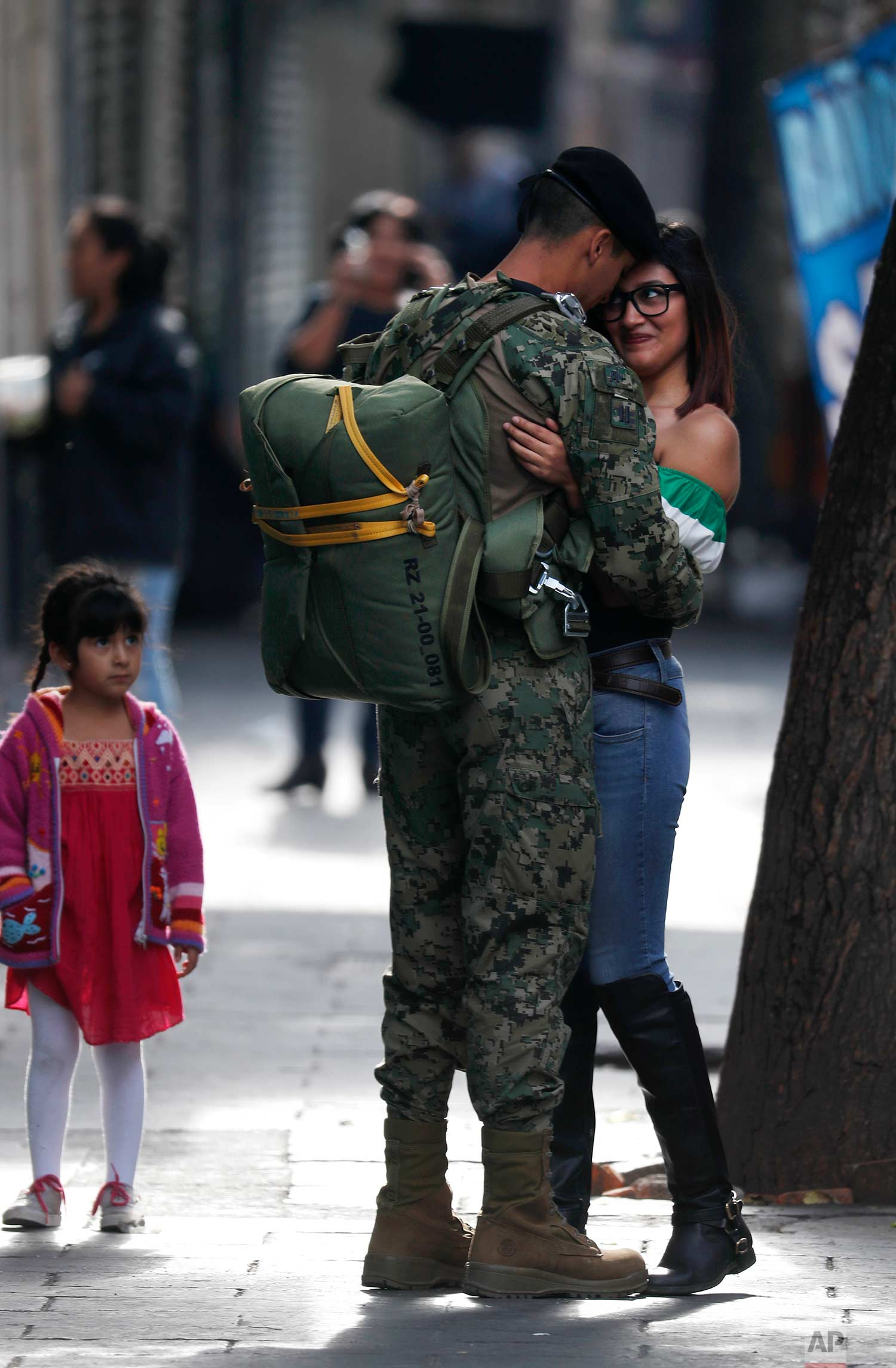 In this Sept. 16, 2017. photo, a soldier embraces a woman before the start of the annual Independence Day military parade in Mexico City's main square, known as the Zocalo. (AP Photo/Eduardo Verdugo)