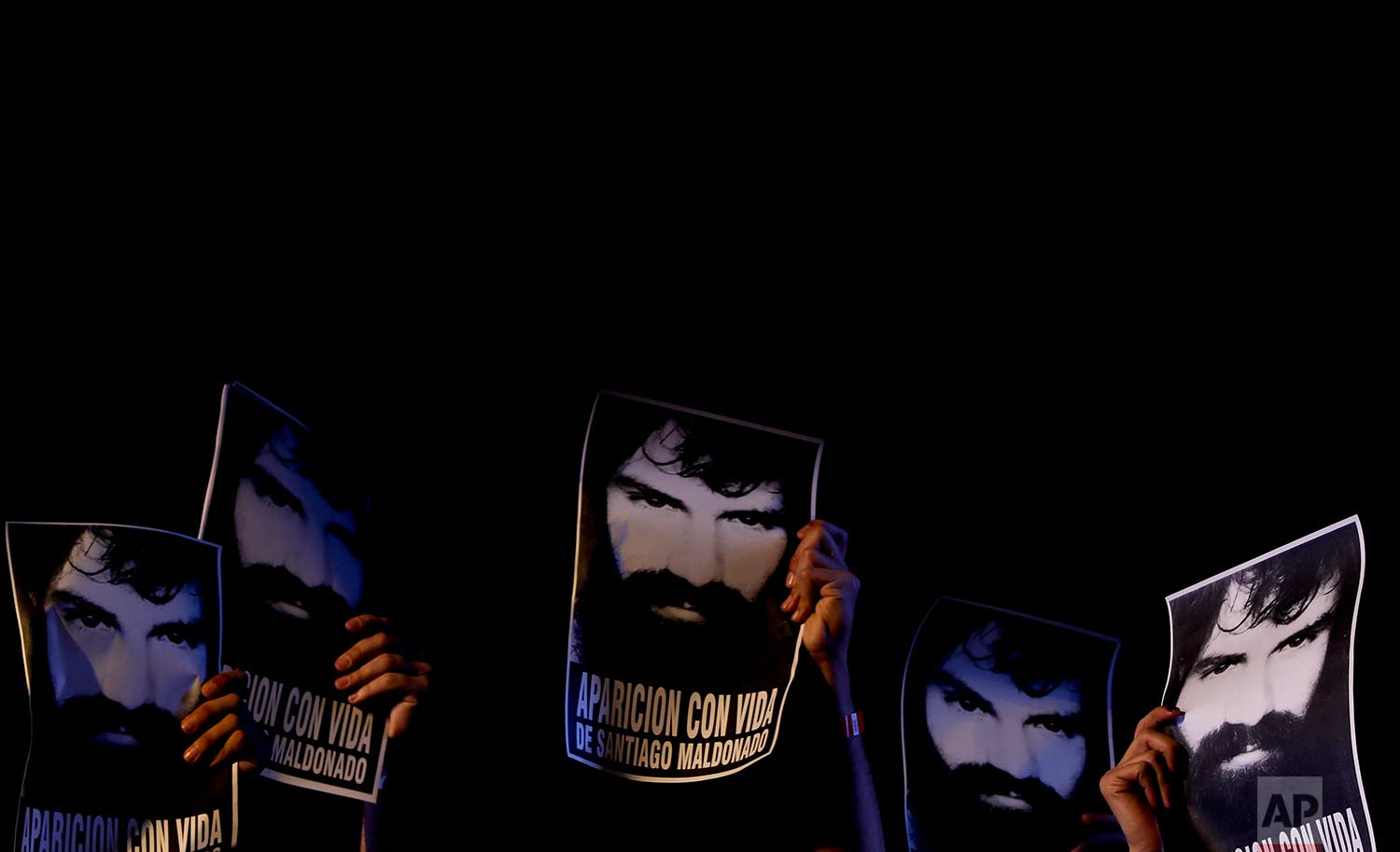 Demonstrators hold photos of missing activist Santiago Maldonado, during a protest at Plaza de Mayo in Buenos Aires, Argentina, Friday, Sept. 1, 2017. (AP Photo/Natacha Pisarenko)