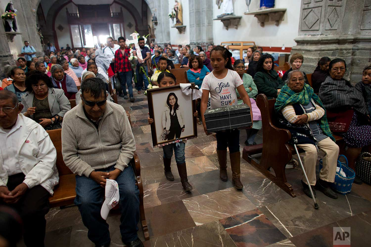 In this Aug. 18, 2017 photo, relatives of murdered doctor and mother, Jessica Sevilla Pedraza, carry a framed portrait of her, a cross, and a box of mementos to be buried alongside her grave, as they arrive for Mass in Villa Cuauhtemoc, Mexico state. (AP Photo/Rebecca Blackwell)