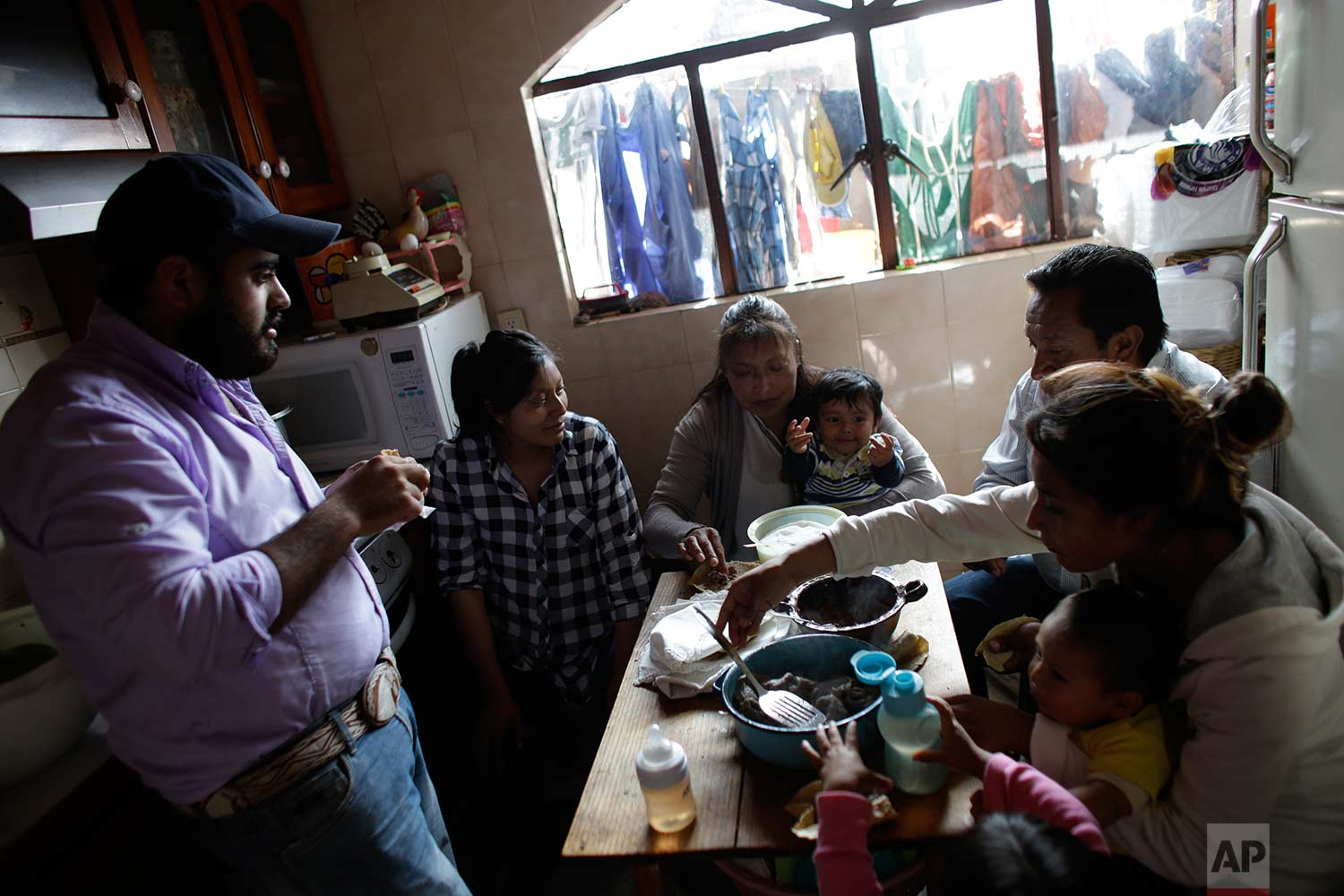 In this Aug. 23, 2017 photo, Juana Pedraza, center, holds her one-year-old grandson Jose Leonardo, who they call Leon, as the family eats breakfast in their home in Villa Cuauhtemoc, Mexico state. (AP Photo/Rebecca Blackwell)