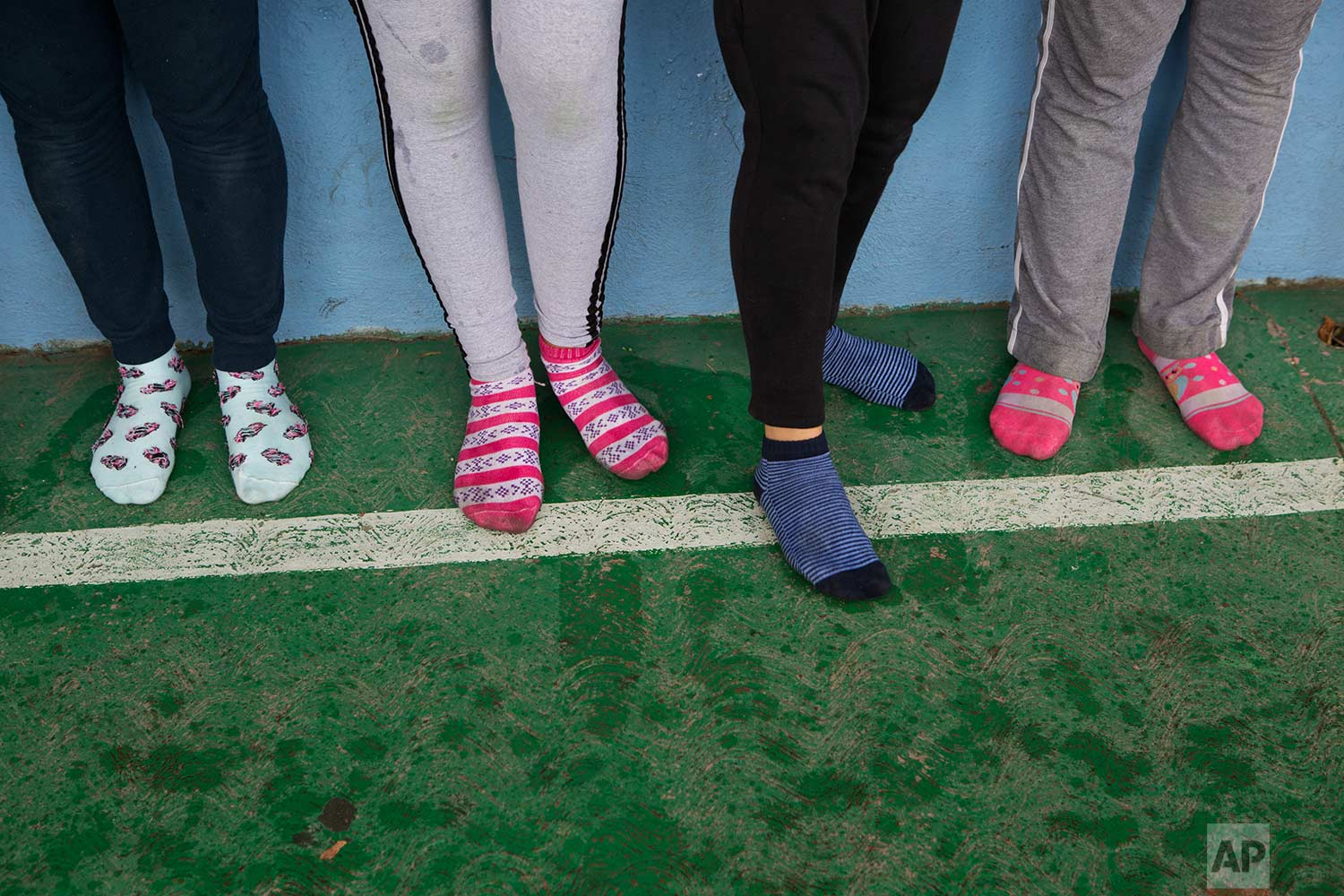 In this Aug. 25, 2017 photo, female nursing students stand in their socks as they take a self-defense workshop led by Muay Thai practitioners in Nezahualcoyotl, Mexico state. (AP Photo/Rebecca Blackwell)