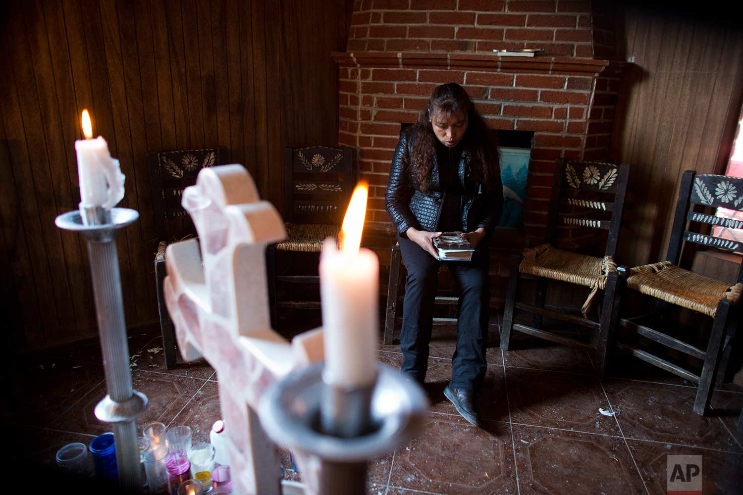In this Aug. 18, 2017 photo, Juana Pedraza sits beside an altar to her 29-year-old daughter, Jessica, inside the family's home in Villa Cuauhtemoc, Mexico state. (AP Photo/Rebecca Blackwell)