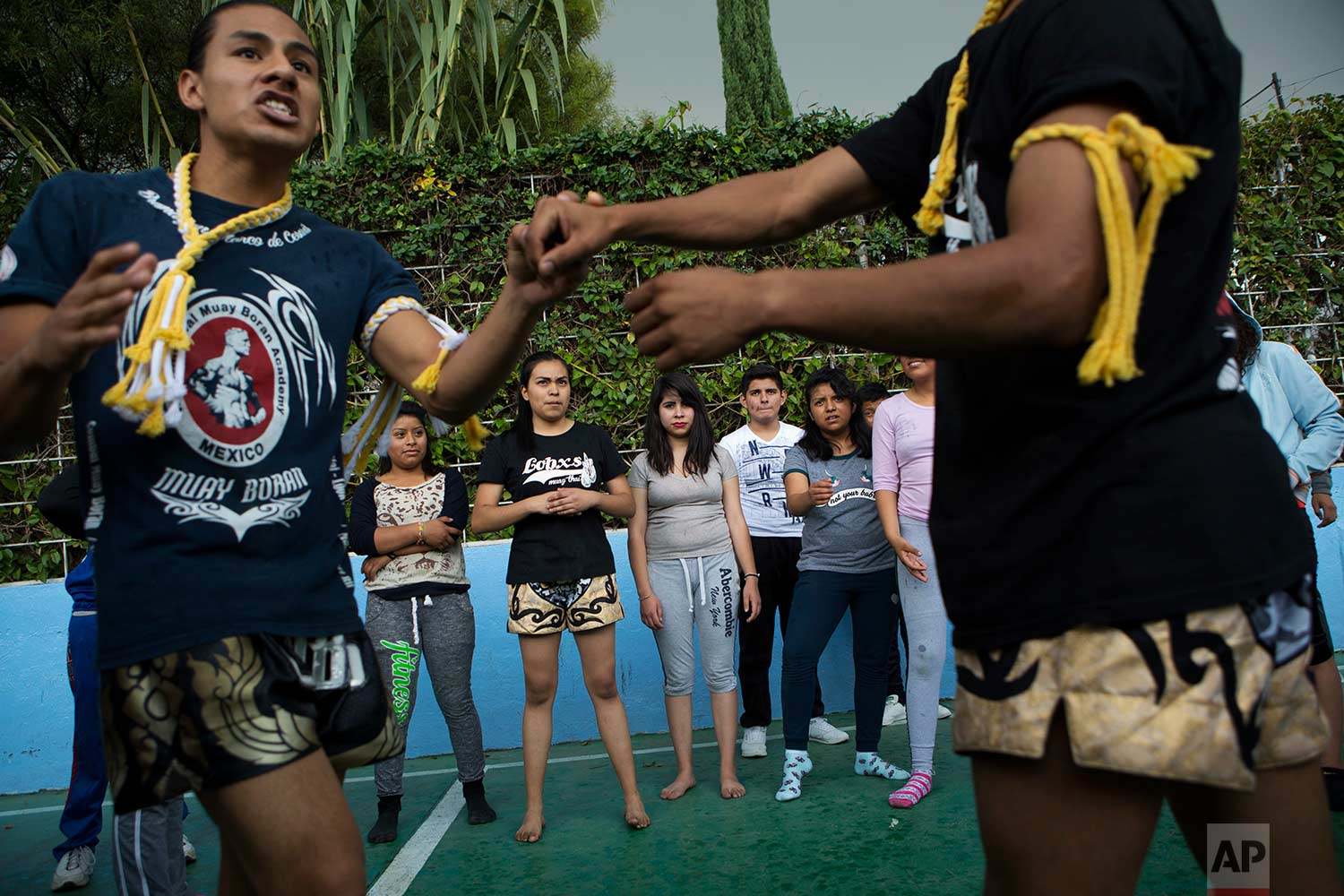 In this Aug. 25, 2017 photo, Muay Thai practitioners demonstrate self-defense moves to mostly female students at a nursing school in Nezahualcoyotl, Mexico state. (AP Photo/Rebecca Blackwell)
