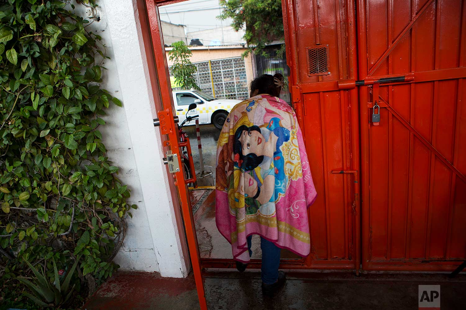 In this Aug. 25, 2017 photo, a cleaning lady looks out the door of a nursing school, monitored by a security guard, in Nezahualcoyotl, Mexico state. (AP Photo/Rebecca Blackwell)