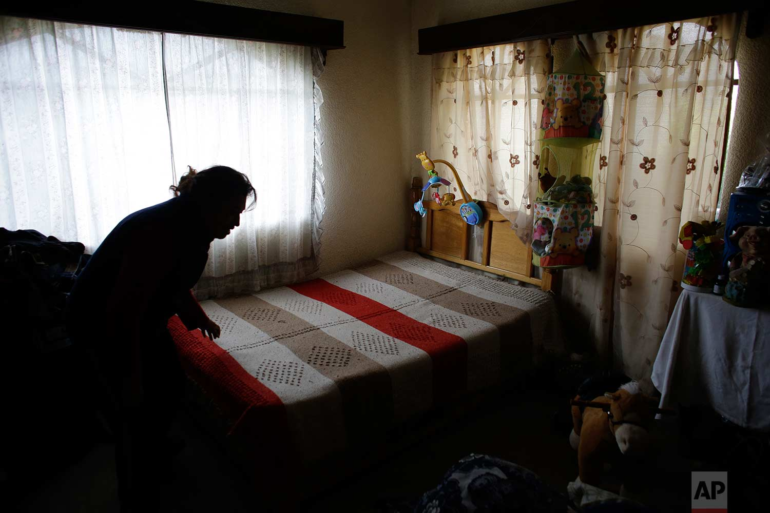 In this Aug. 23, 2017 photo, Juana Pedraza makes the bed in the room her daughter Jessica shared with her one-year-old son in the family's home in Villa Cuauhtemoc, (AP Photo/Rebecca Blackwell)