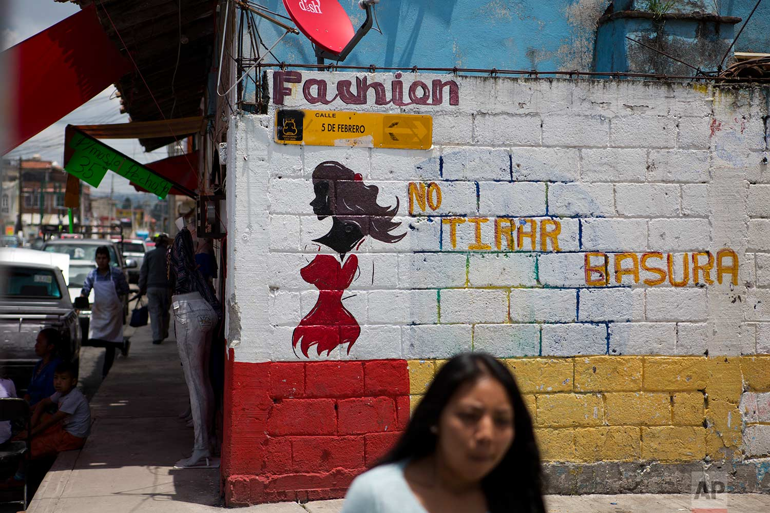 "In this Aug. 18, 2017 photo, a woman walks past the wall of a clothing store painted with the figure of a woman as advertising, next to phrase ""No dumping garbage,"" in Villa Cuauhtemoc, Mexico state. ""This problem is difficult to eradicate because it is rooted in ideas that assume that we as women are worth less than men, that we as women can be treated like trash,"" said Dilcya Garcia Espinoza de los Monteros, deputy state prosecutor for gender violence crimes, regarding femicides. (AP Photo/Rebecca Blackwell)"