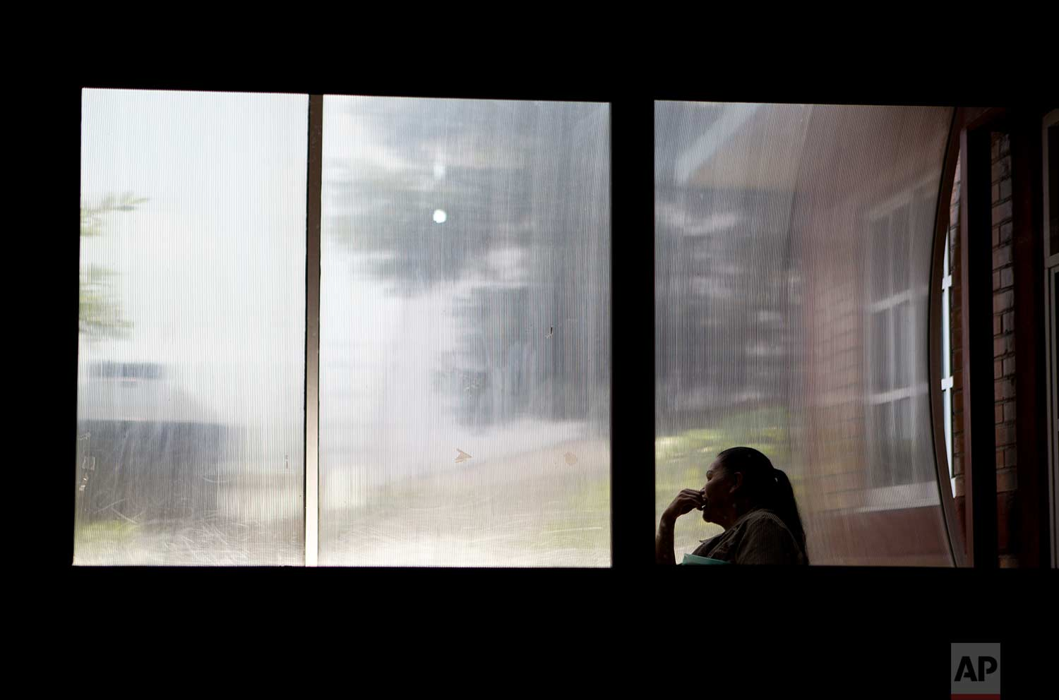 In this Aug. 15, 2007 photo, a woman sits in front of a window inside a nursing school in Nezahualcoyotl, Mexico state. The nonprofit Citizen Observatory Against Gender Violence, Disappearance and Femicides in Mexico State counted 263 femicides in 2016 alone. (AP Photo/Rebecca Blackwell)
