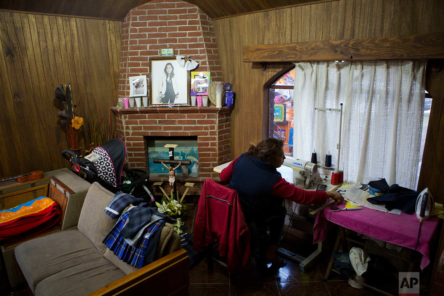 In this Aug. 23, 2017 photo, Juana Pedraza sits next to a small altar in honor of her oldest daughter Jessica, who was murdered at age 29, as she sews school uniforms to order at her home in Villa Cuauhtemoc, Mexico state. (AP Photo/Rebecca Blackwell)