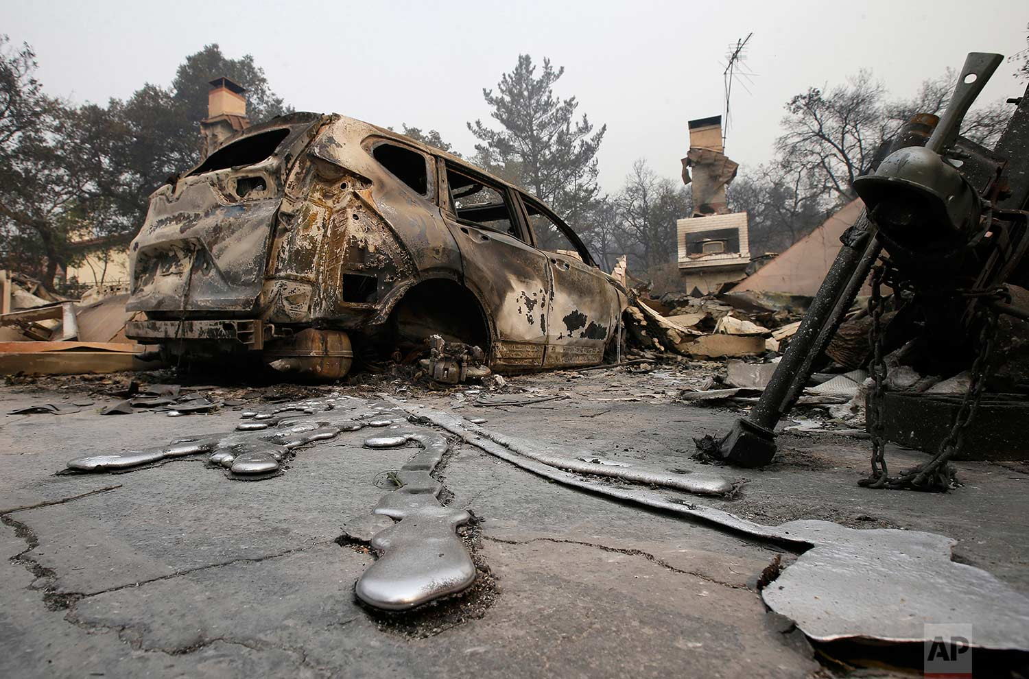 Streams of solidified melted metal reach out from a destroyed vehicle parked at a home Tuesday, Oct. 10, 2017, after a wildfire near Napa, Calif. (AP Photo/Rich Pedroncelli)