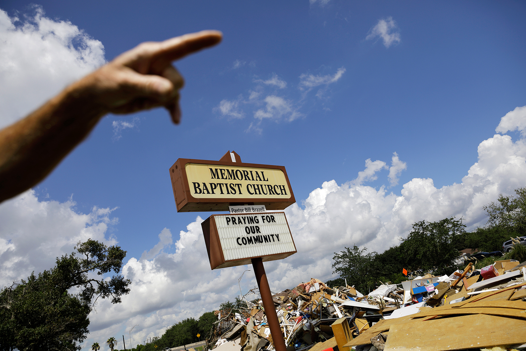 """Debris sits outside the Memorial Baptist Church in Port Arthur, Texas, Monday, Sept. 25, 2017. It was damaged by Hurricane Harvey floodwaters. Church member Wayne Christopher said, """"You know what it said up there? We were so busy working we didn't notice. Then one day we looked up and it said, 'you've got problems, we have the solution,'"""" Christopher's wife Polly remembers. """"We said, 'we might need to change the sign.'"""" Because she's not sure that they have solutions for this. Now their sign reads: Praying for our Community."""" (AP Photo/David Goldman)"""