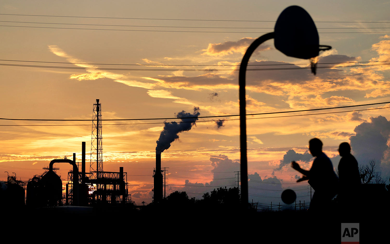 An oil refinery stands in the background as children play on a basketball court in Port Arthur, Texas, Wednesday, Sept. 27, 2017. The region's economy is tied to the petroleum industry more than in any other place in America: the concentration of people here employed by refineries is 81 times higher than the rest of the country. (AP Photo/David Goldman)