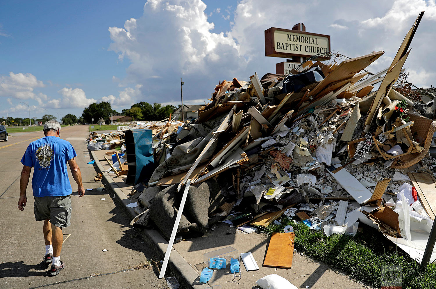 """Wayne Christopher walks by a pile of debris outside the church he'd attended his whole life damaged from Hurricane Harvey in Port Arthur, Texas, Monday, Sept. 25, 2017. He and his wife had come here every Sunday and every Wednesday for more than four decades. This church is where he was baptized, where he met his high school sweetheart, then married her 46 years ago. """"We have a lot of memories here. This is my home. I've been here all my life,"""" said Christopher. (AP Photo/David Goldman)"""