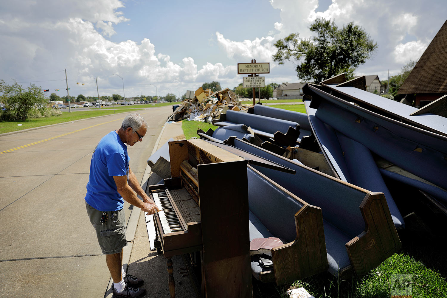 """Wayne Christopher plays the keys on a piano put out on the curb in Port Arthur, Texas, Monday, Sept. 25, 2017, next to pews from the Memorial Baptist Church which he'd attended his whole life. The damage was caused by Hurricane Harvey a month earlier. """"He's not too up on global warming, and that's a shame,"""" Christopher said of the president he supported in November, and supports still. He also believes in the consensus among scientists that climate change is real and that this disastrous run of weather, from droughts in the west to wildfires to catastrophic hurricanes along the coasts, is a preview of the future if the country doesn't begin to take the problem seriously. (AP Photo/David Goldman)"""