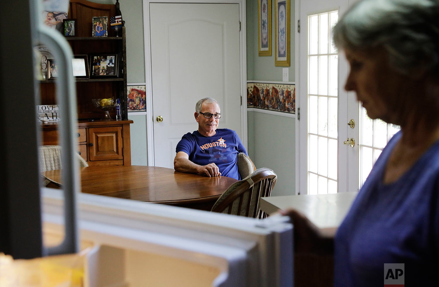 """Wayne Christopher sits in the kitchen of his home with his wife Polly in Nederland, Texas, Tuesday, Sept. 26, 2017. Christopher thinks Trump has a responsibility to seek the truth and act accordingly, for future generations. """"He's got a business mind, whatever it takes to make money, that's what he's going to do, to make America great again,"""" Christopher said, and that's why he voted for him. """"But it does make me wonder if he looks at global warming as a real harm. Because you can make all the money in the world here. But if you don't have a world, what good is it going to do you?"""" (AP Photo/David Goldman)"""