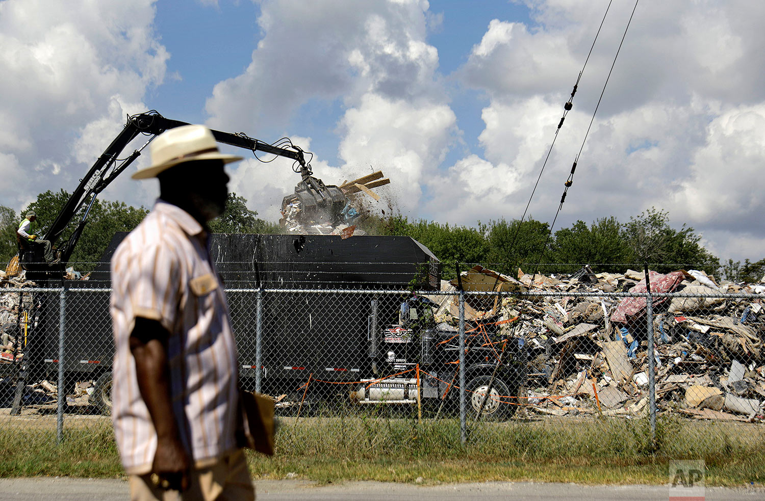 """Hilton Kelley walks by as a truck unloads flood damaged debris at a makeshift dump across the street from a residential neighborhood in Port Arthur, Texas, Wednesday, Sept. 27, 2017. Kelley is fighting to get the dump shut down for fear of nearby residents breathing in mold. Kelley says many people in Port Arthur understand the impact local industry has on climate change and pollution. But he says they're often hesitant to speak out. """"When you have people living at or below the poverty line, many people are hopeful of getting jobs at those refineries or chemical plants."""" (AP Photo/David Goldman)"""